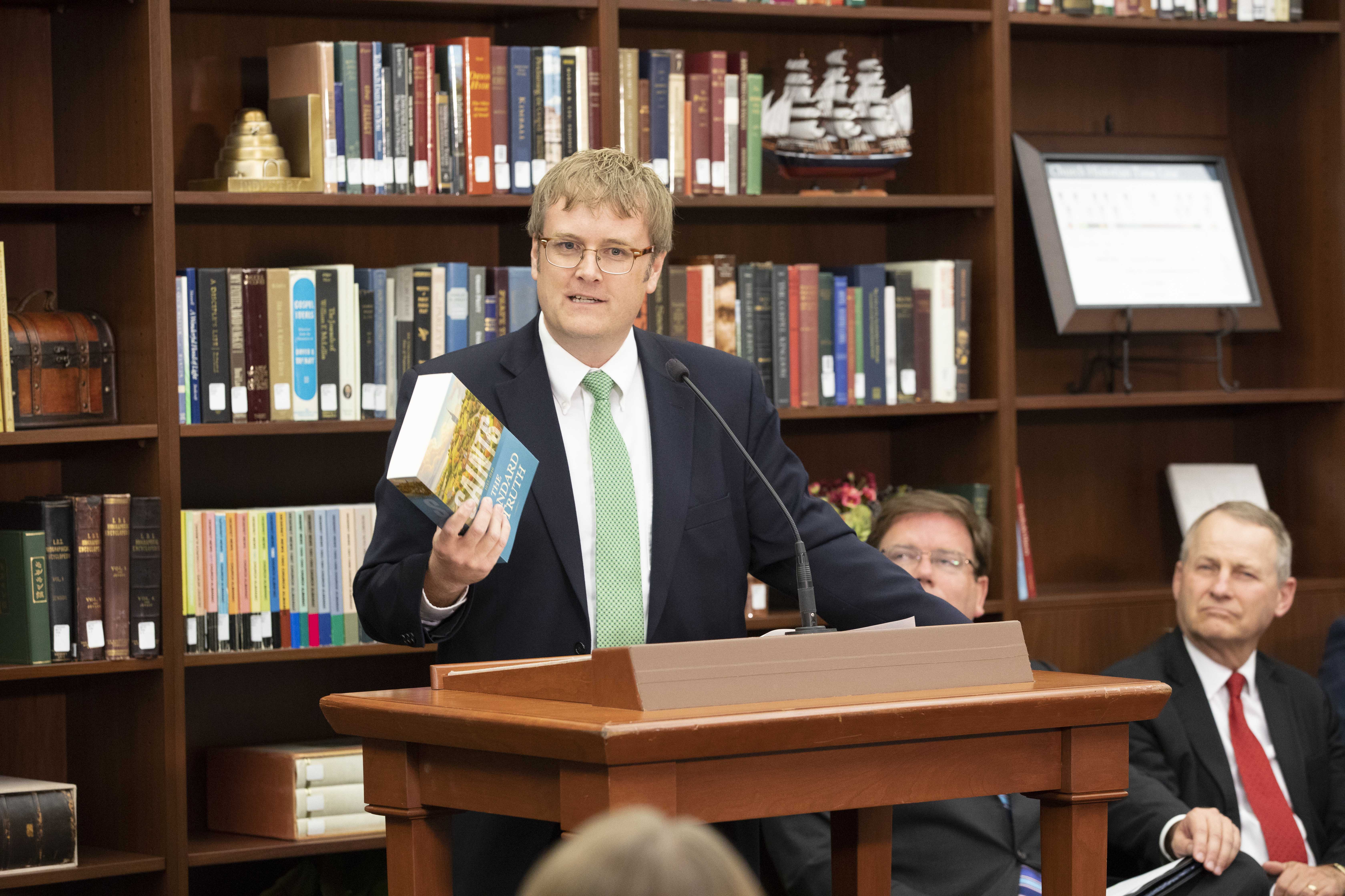 "Matthew J. Grow, director of publications of the Church History Department, holds a copy of ""Saints: The Standard of Truth,"" during Tuesday's press conference."