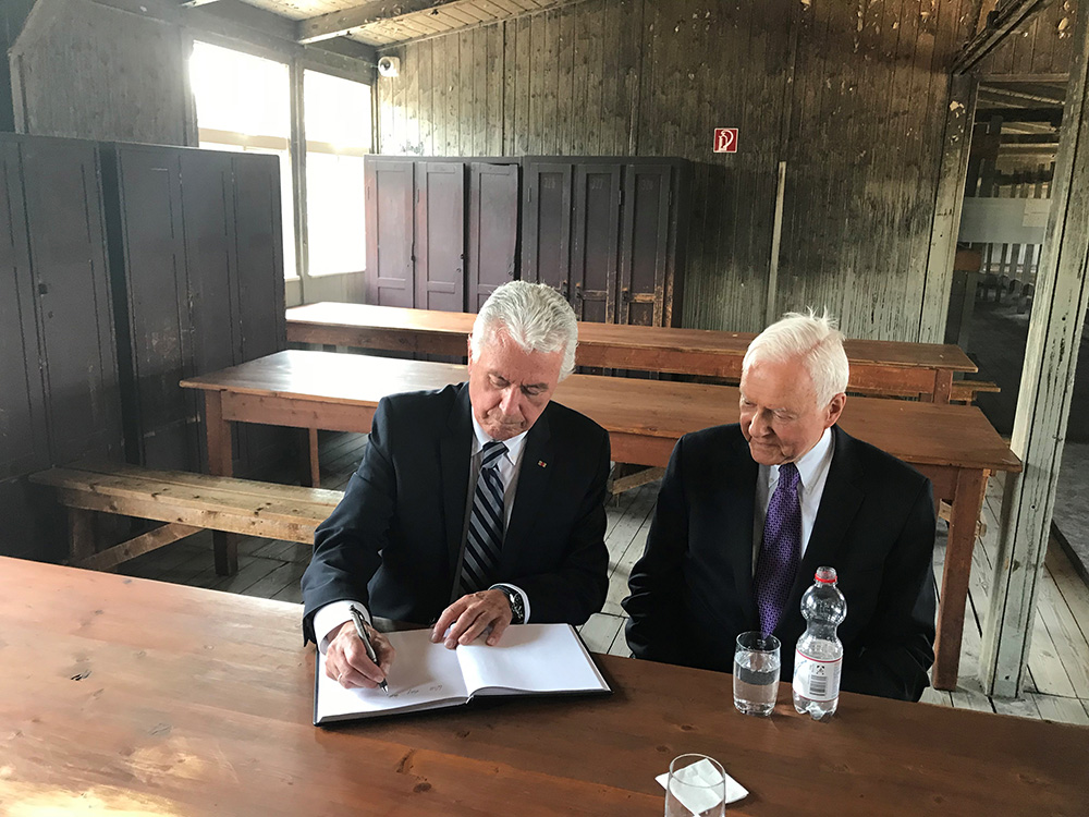 Elder Dieter F. Uchtdorf of the Quorum of the Twelve Apostles and U.S. Sen. Orrin Hatch of Utah sign a guest book while sitting in one of the prisoner barracks of the Sachsenhausen concentration camp in Oranienburg, Germany, July 5, 2018.