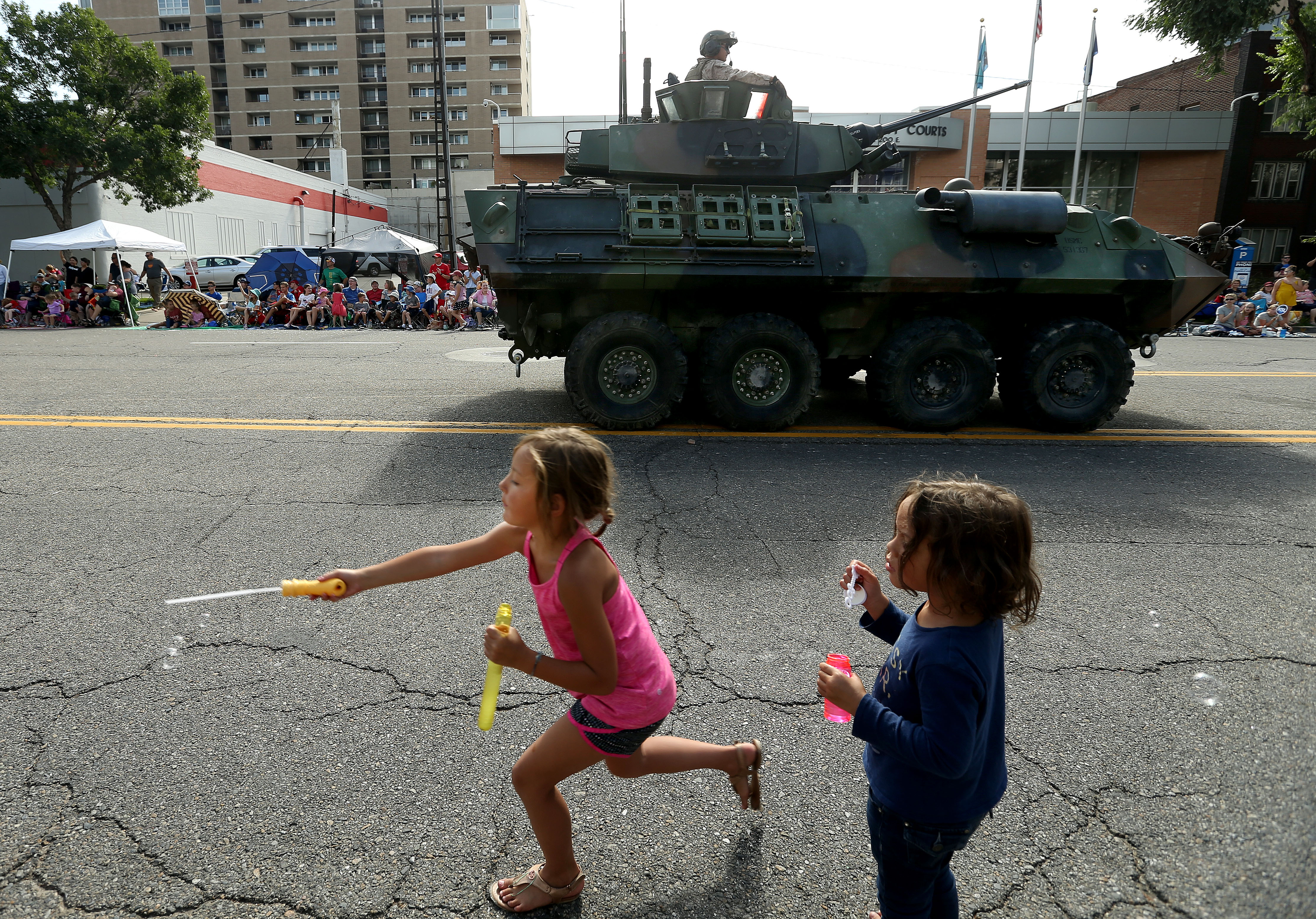 Children play with bubbles a the Marines pass by during the Days of '47 Parade in Salt Lake City on Wednesday, July 24, 2019.