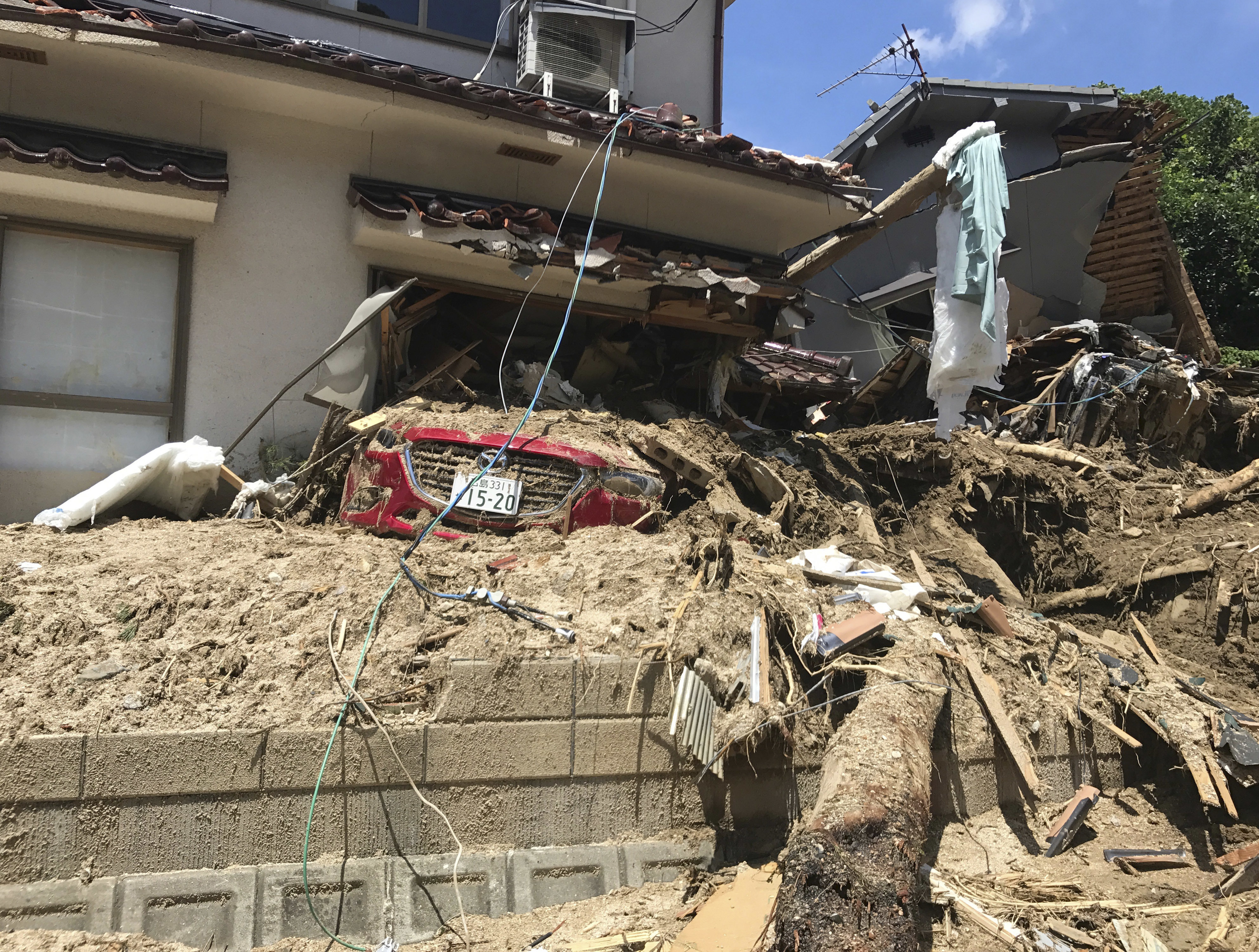 A car is covered with mud as houses are damaged after a mudslide caused by heavy rains in Hiroshima, southwestern Japan, Tuesday, July 10, 2018. Rescuers combed through mud-covered hillsides and along riverbanks searching for dozens of people missing after heavy rains unleashed flooding and mudslides in southwestern Japan.