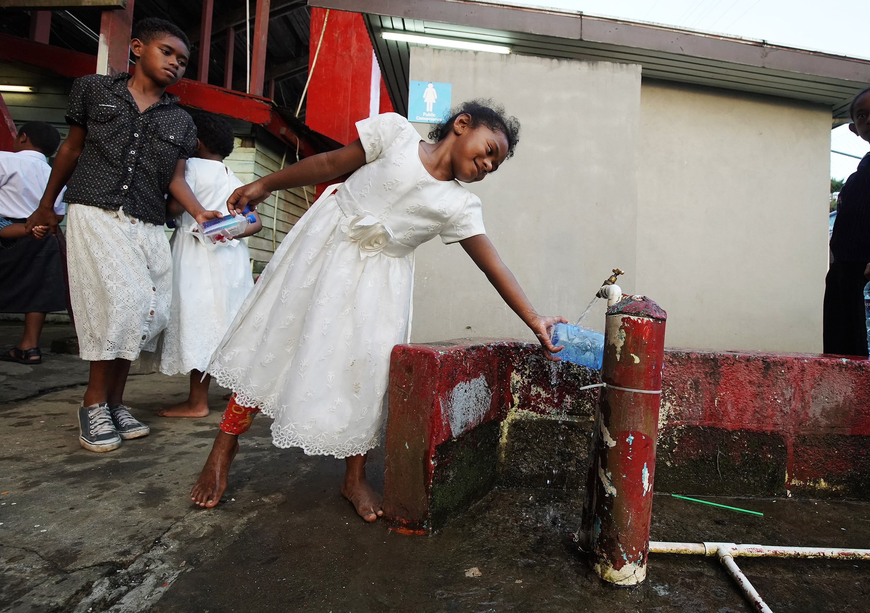 Crystal Rabukara gathers water during a devotional at Ratu Cakobau stadium in Nausori, Fiji on May 22, 2019.