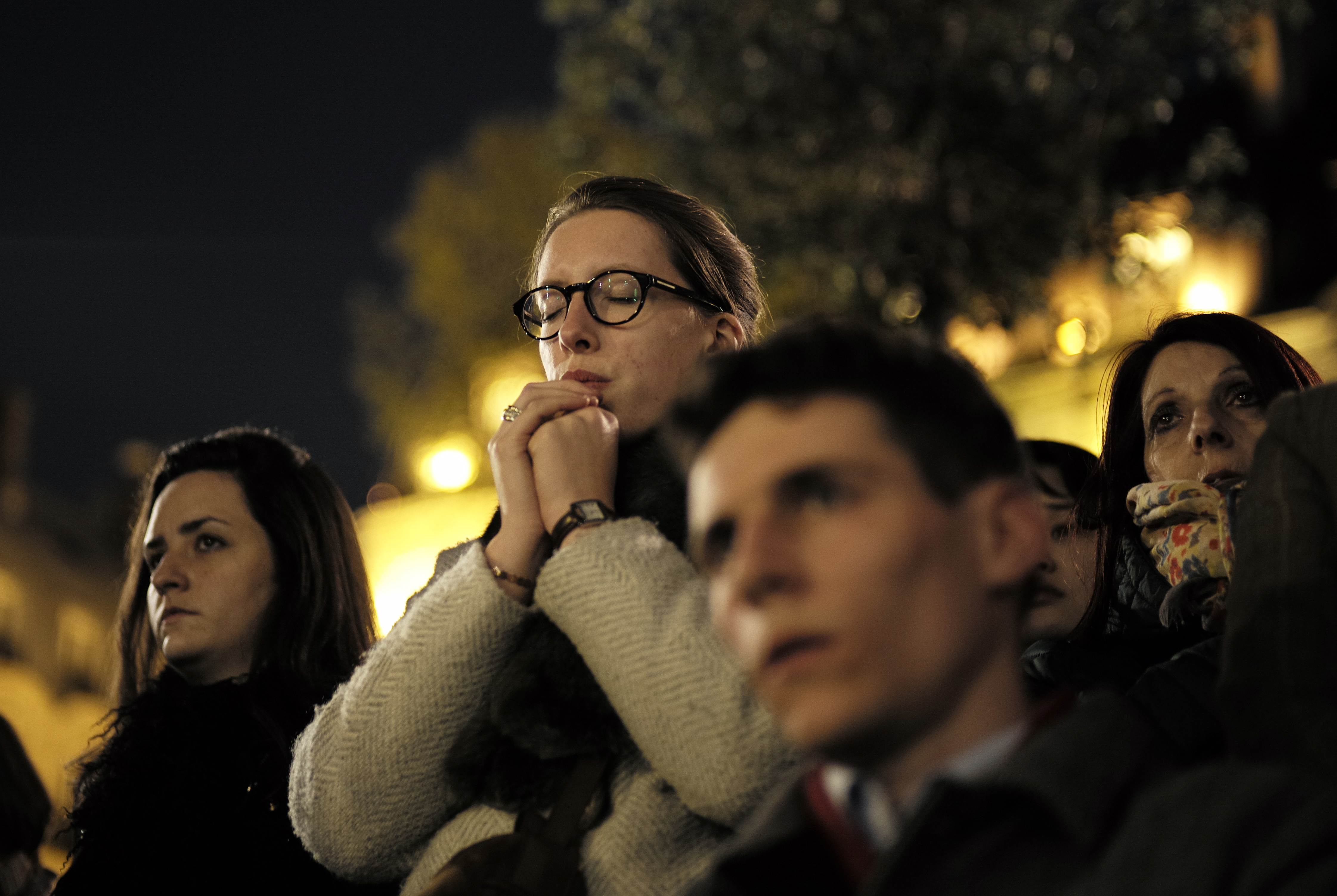 People attend a vigil in Paris, Tuesday April 16, 2019. Firefighters declared success Tuesday in a more than 12-hour battle to extinguish an inferno engulfing Paris' iconic Notre Dame cathedral that claimed its spire and roof but spared its bell towers.