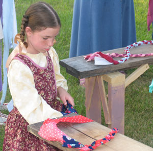 Emily Pipe learns rug braiding in pre-show activity in connection with new Nauvoo Pageant.