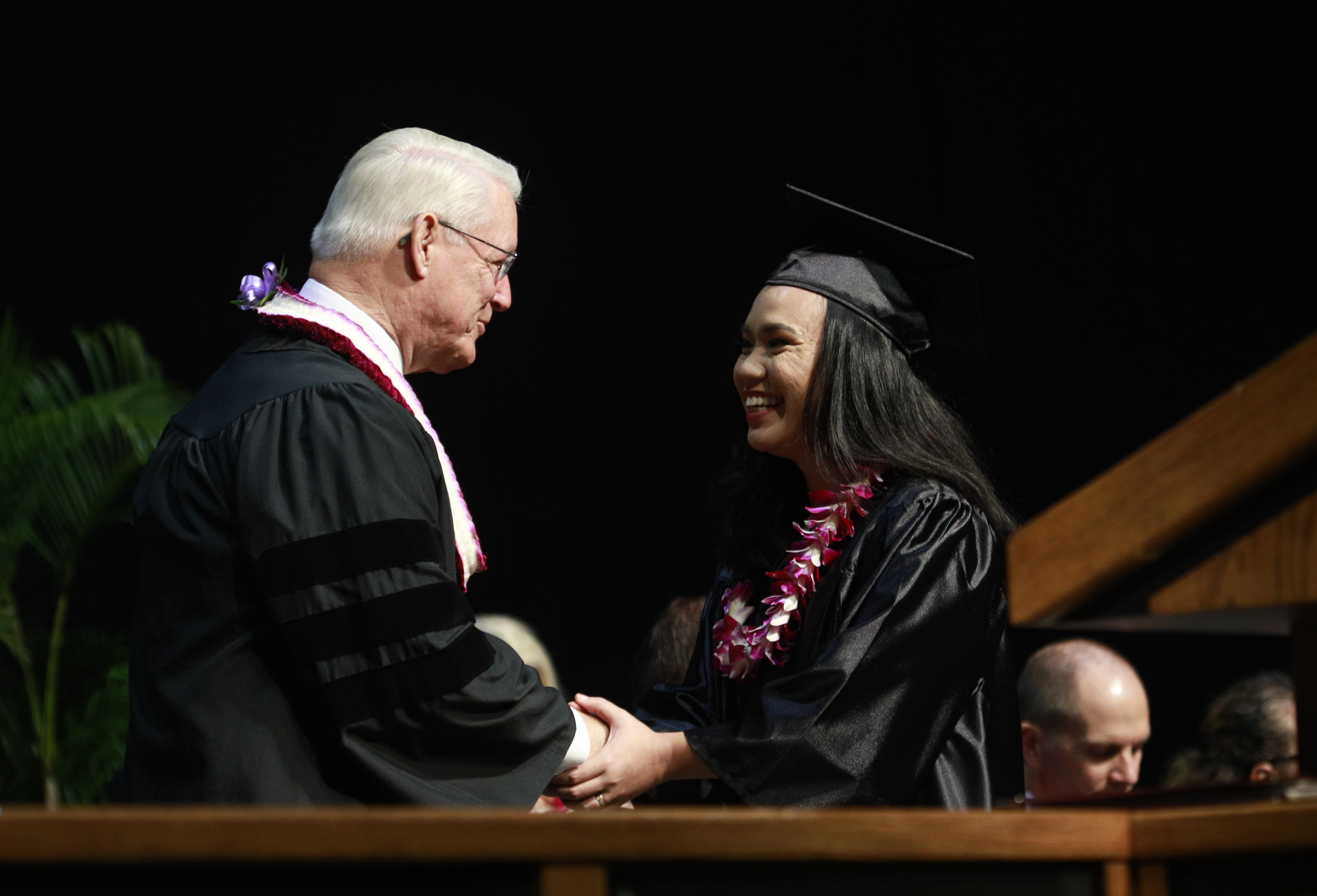 Bishop Dean M. Davies of the Presiding Bishopric shakes hands with a graduate after BYU-Hawaii graduation on June 30.