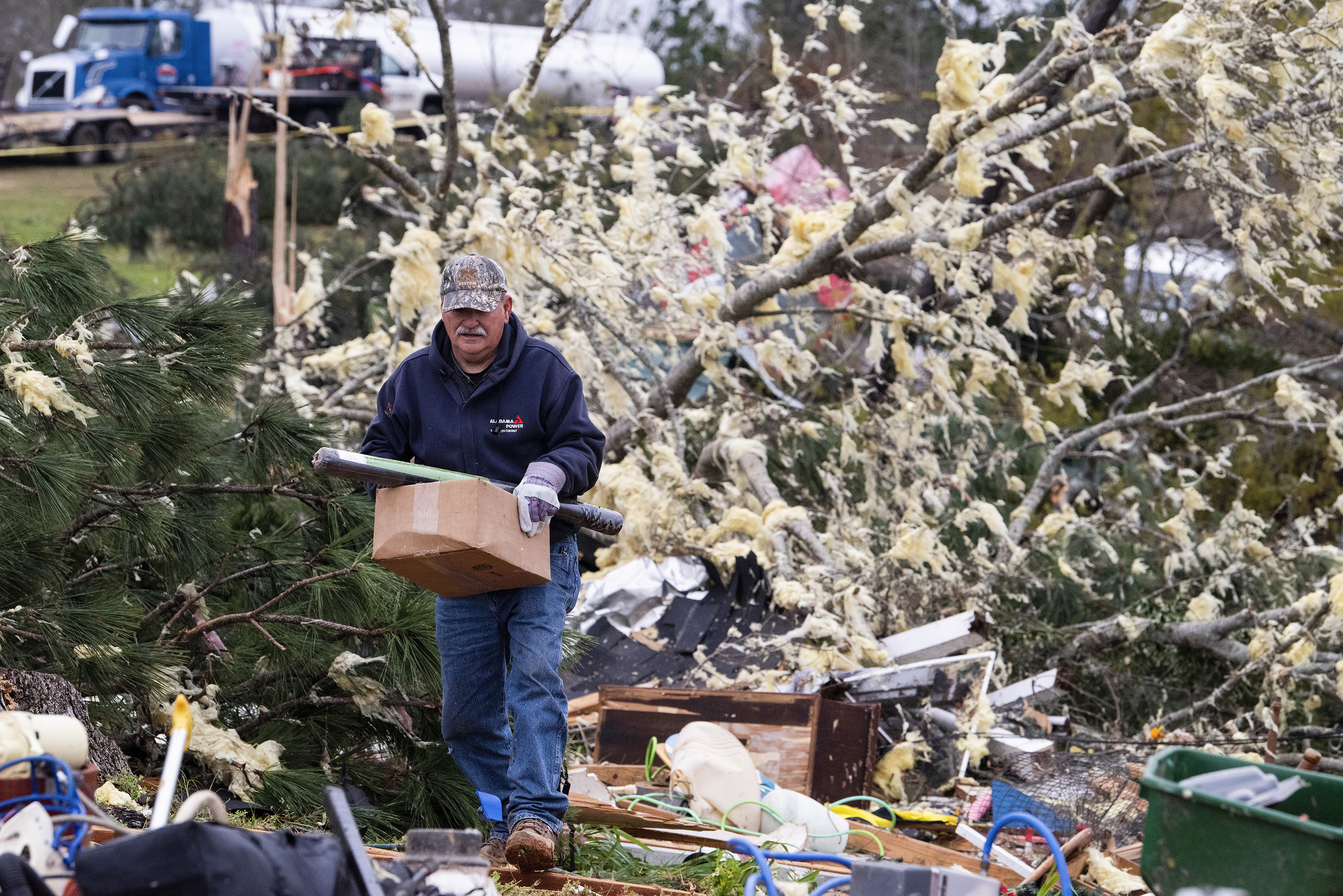 A man salvages belongings near Beauregard, Ala., on Monday March 4, 2019. Friends in eastern Alabama are helping tornado survivors retrieve the scattered pieces of their lives after devastating winds destroyed their homes and killed at least 23 people. (Mickey Welsh/Montgomery Advertiser via AP)