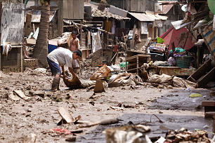 Residents remove debris in a mud-covered residential area of Manila. Evacuees slowly return to their homes to clear mud and debris that swamped their area after days of rain submerged much of the city.