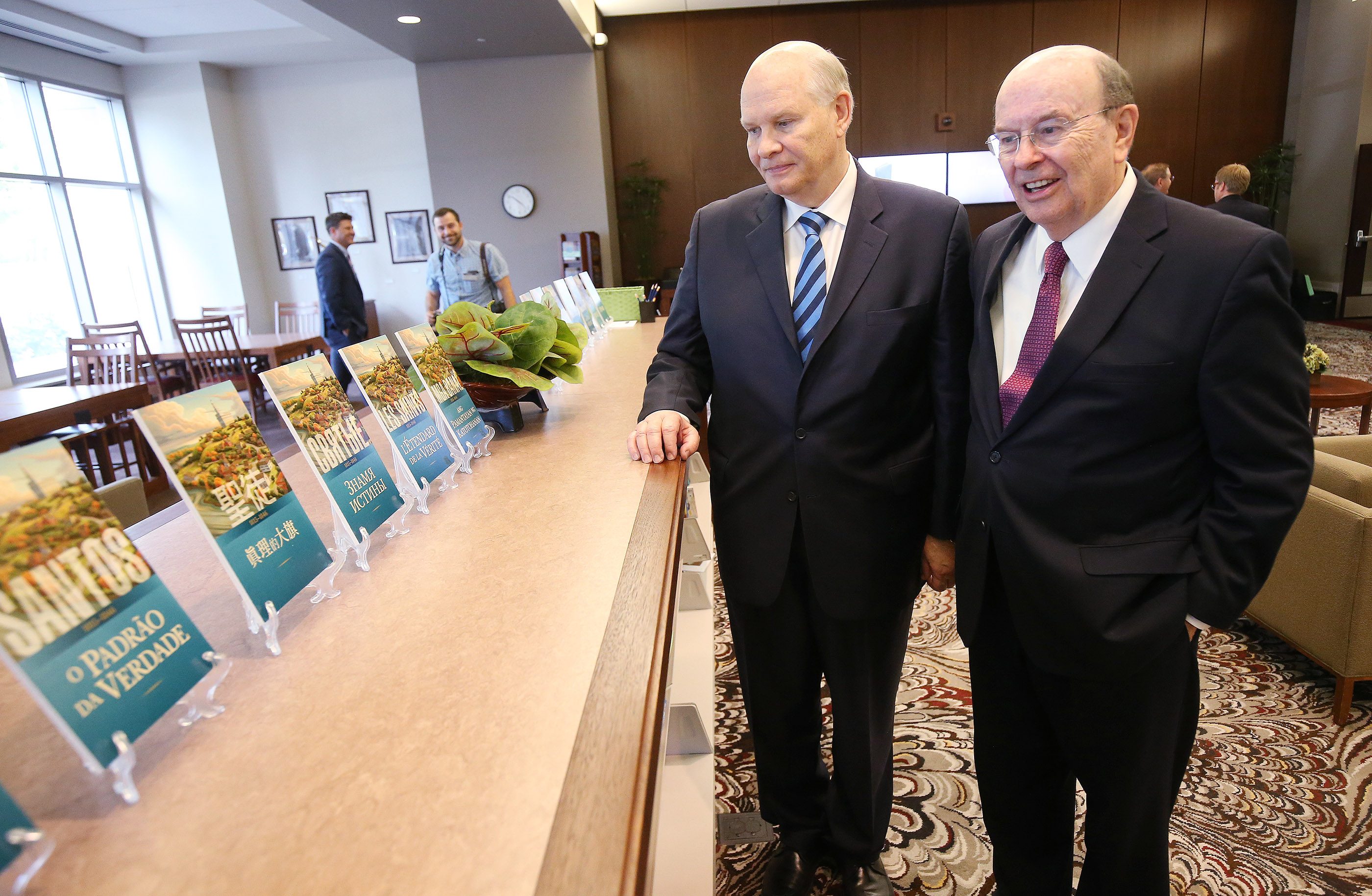 """Elder Dale G. Renlund and Elder Quentin L. Cook, both of the Quorum of the Twelve Apostles, look over different language editions of """"Saints: The Story of the Church of Jesus Christ in the Latter Days"""" in Salt Lake City on Tuesday, Sept. 4, 2018."""