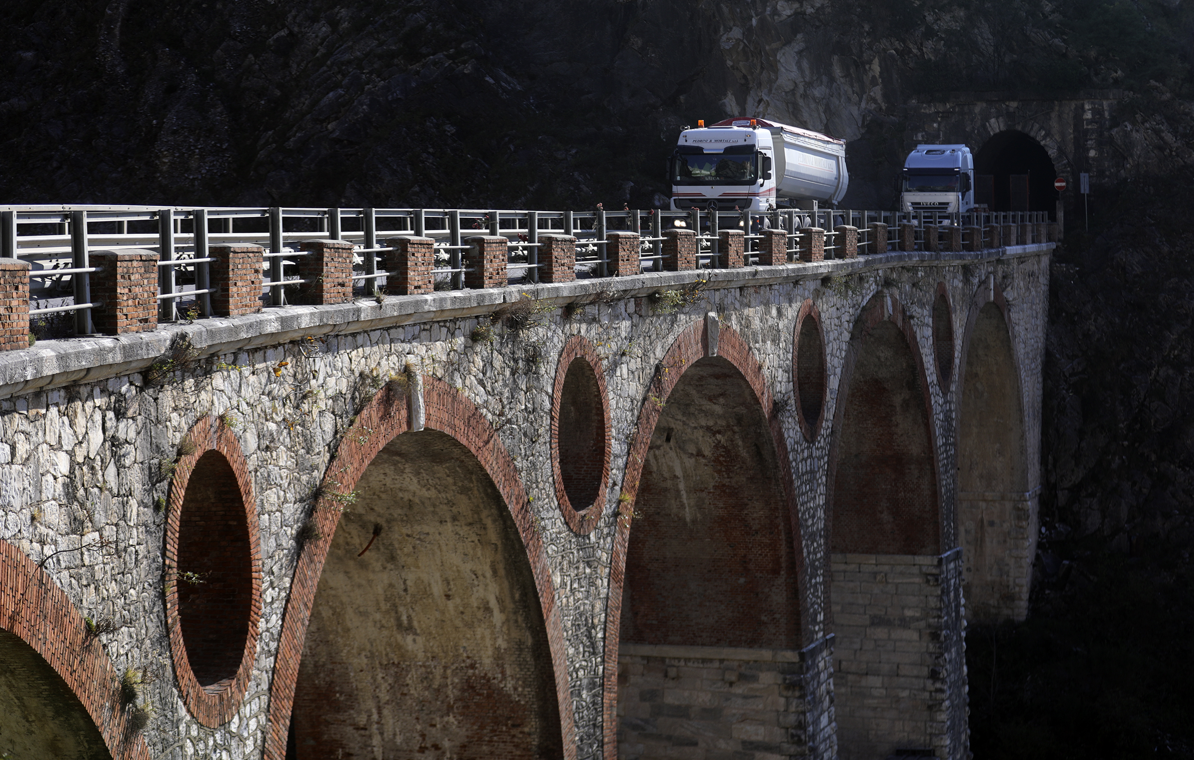 Trucks travel over a bridge at the base of marble quarries in Carrara, Italy, on Thursday, Nov. 15, 2018.