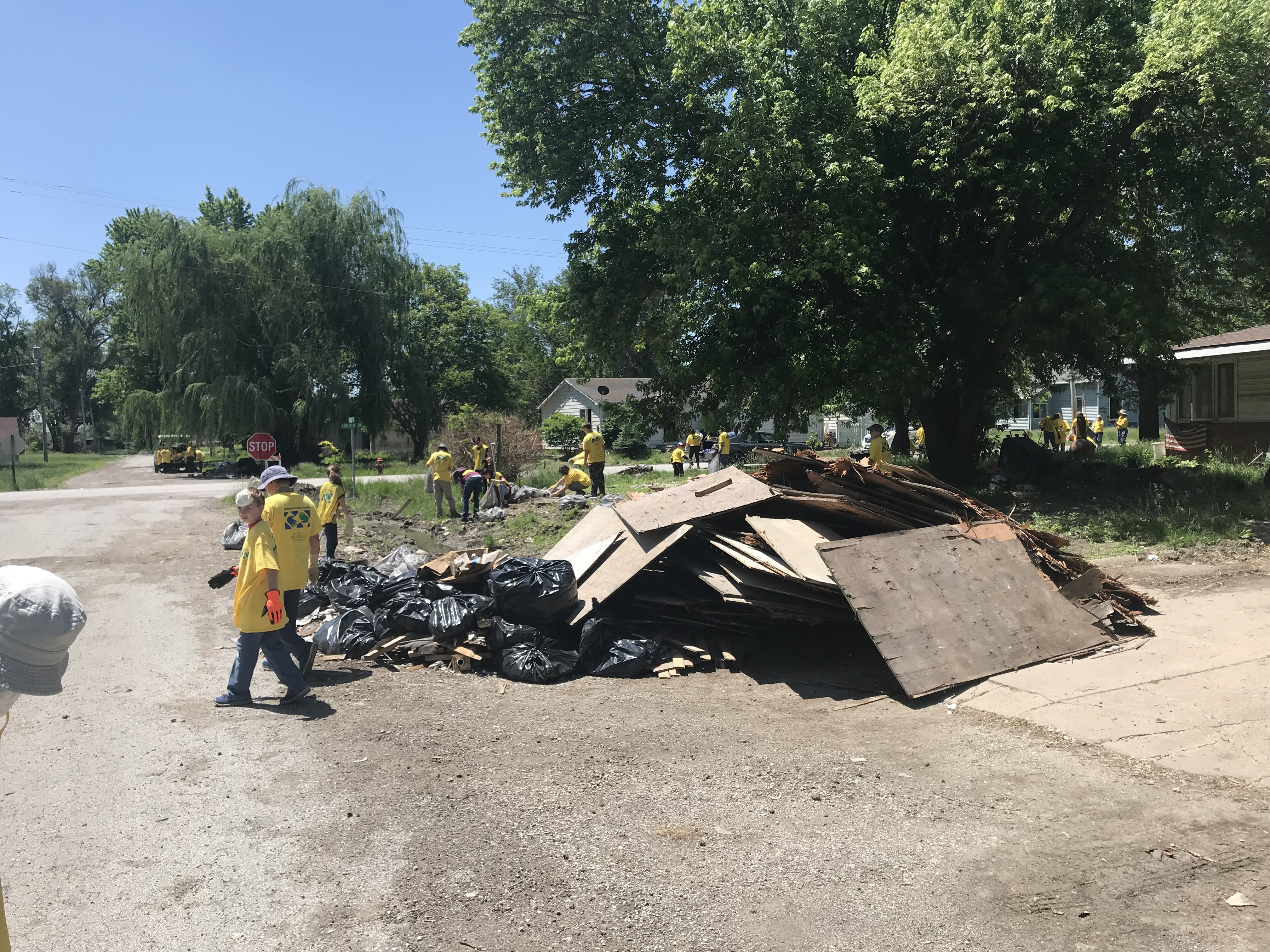Youth and leaders from 8 stakes serve the people impacted by devastating floods by cleaning up streets and homes in Pacific Junction, Iowa on June 10, 2019.