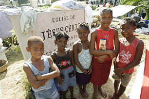Unidentified children stand near the Central Ward Church sign as they live on the grounds in Prince Au Port, Haiti.