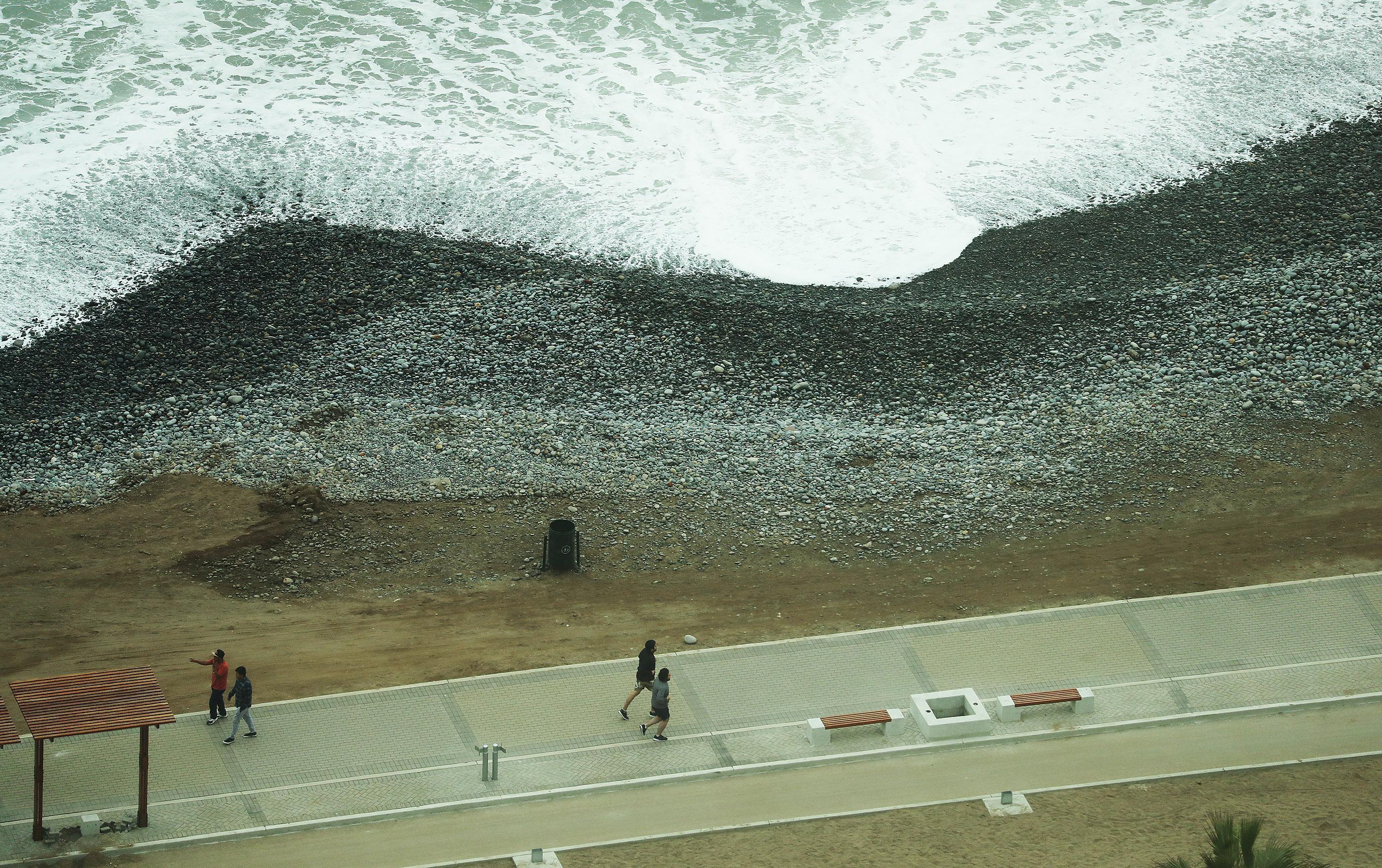 People walk near Redondo Beach in Lima, Peru, on Oct. 20, 2018.