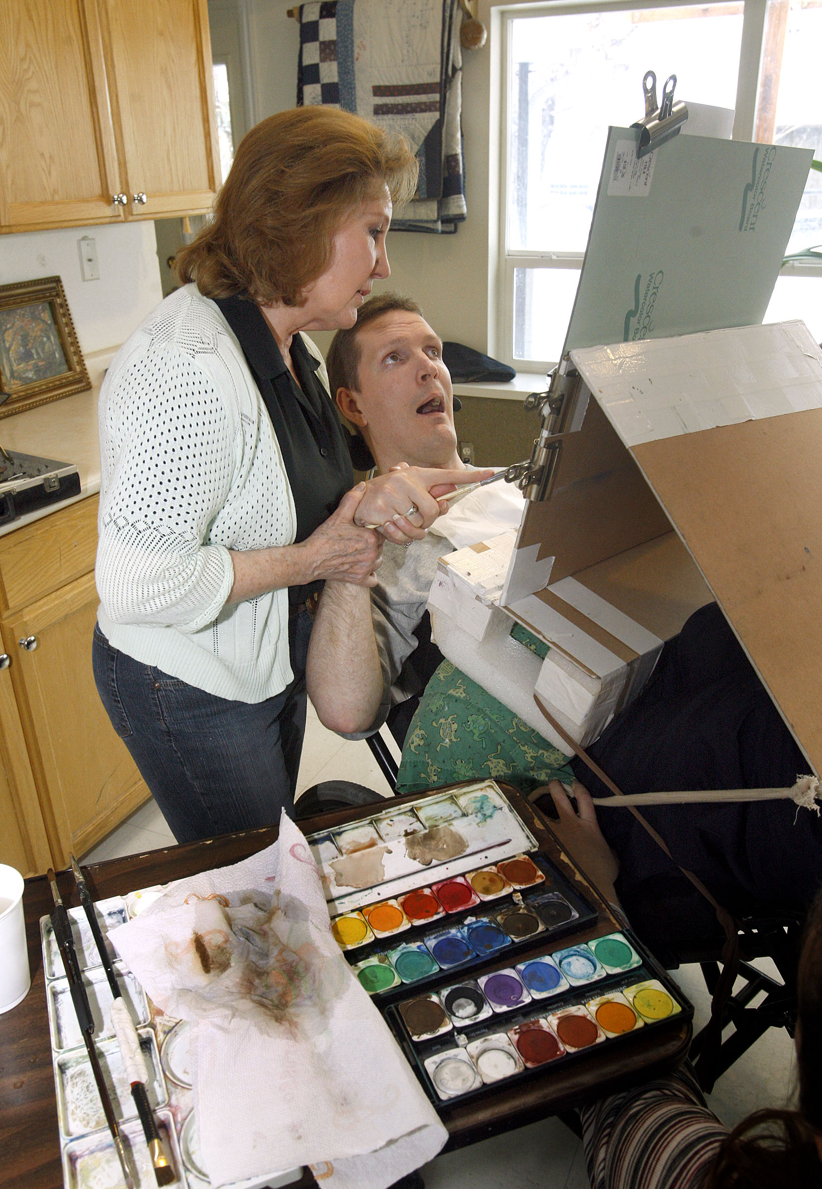 Carol Harding helps Orin Voorheis paint a water color painting of his parents. Harding holds his arm up and shows him where to paint, but Voorheis makes the strokes and chooses the colors he wants to use in his paintings.