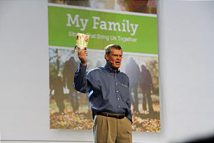 """Elder Dennis C. Brimhall, CEO of FamilySearch International and an Area Seventy of the Church, holds up copy of """"My Family"""" booklet during his address at keynote session of RootsTech 2014 Feb. 6."""