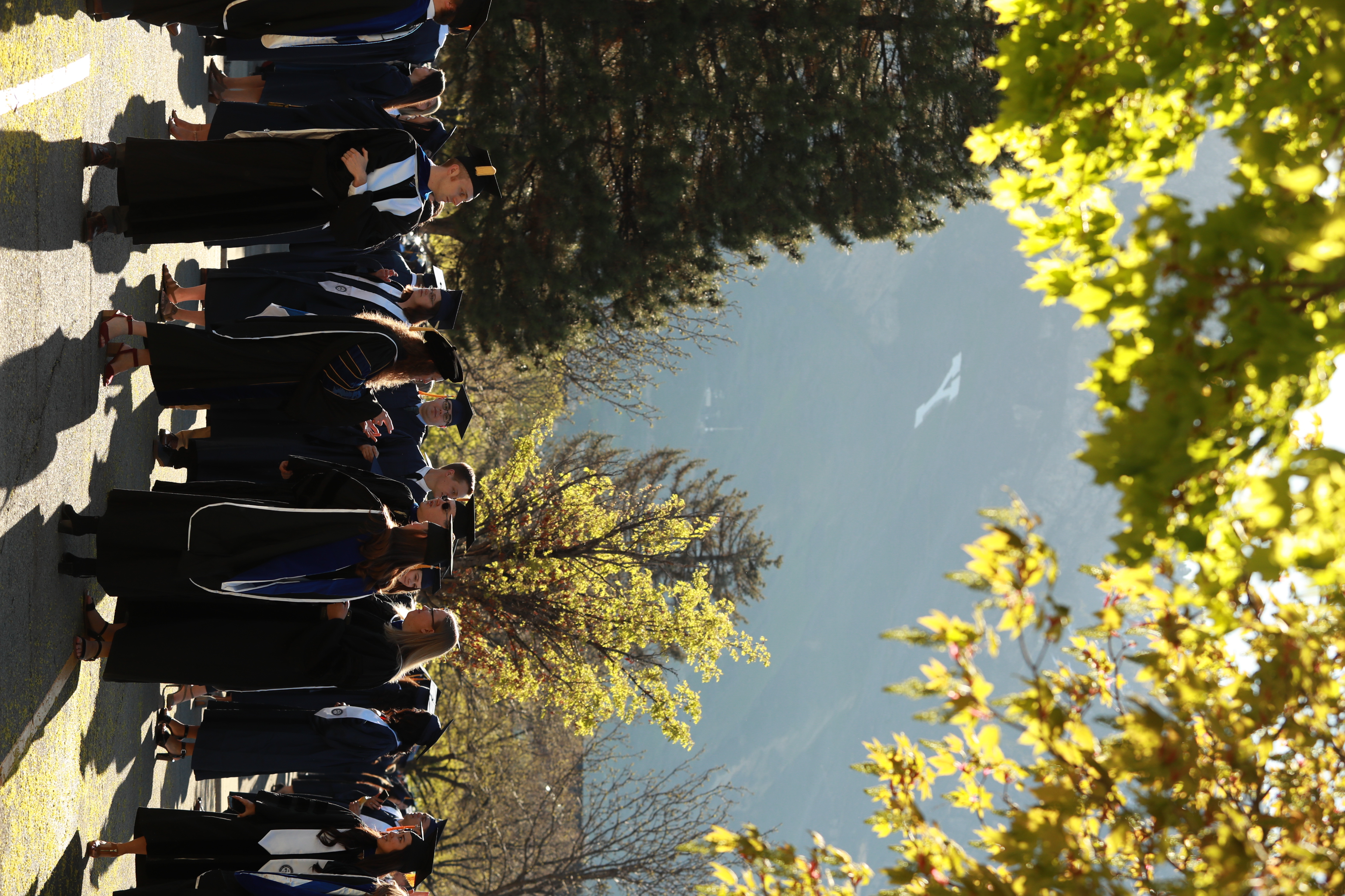 With Y Mountain in the background, new BYU graduates gather prior to April 25, 2019, commencement exercises.