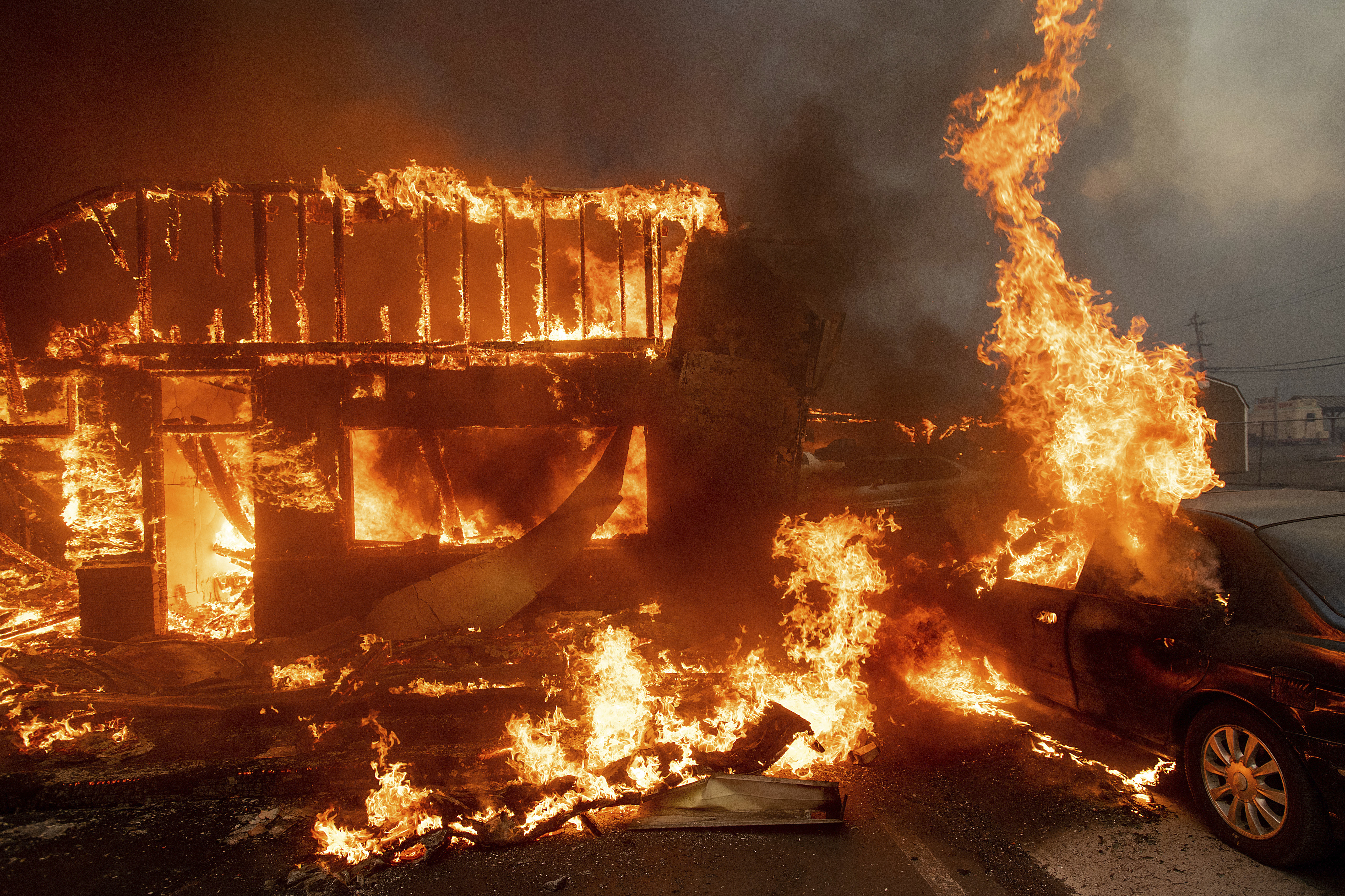 Flames consume a car and building as Camp Fire tears through Paradise, Calif., on Thursday, Nov. 8, 2018.