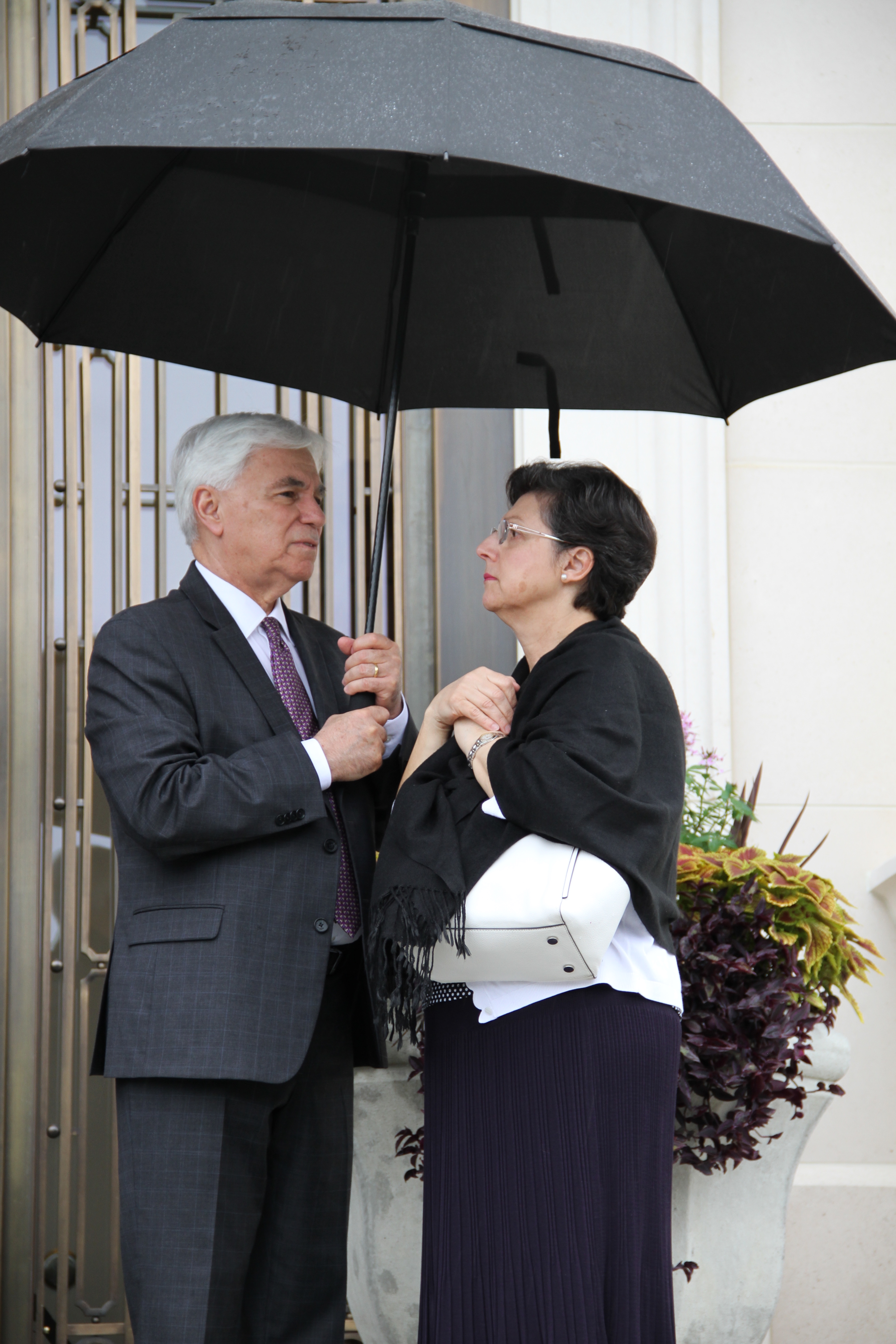 Elder Claudio R. M. Costa and Sister Margareth Costa stand under an umbrella near the entrance to the Memphis Tennessee Temple on May 4, 2019.