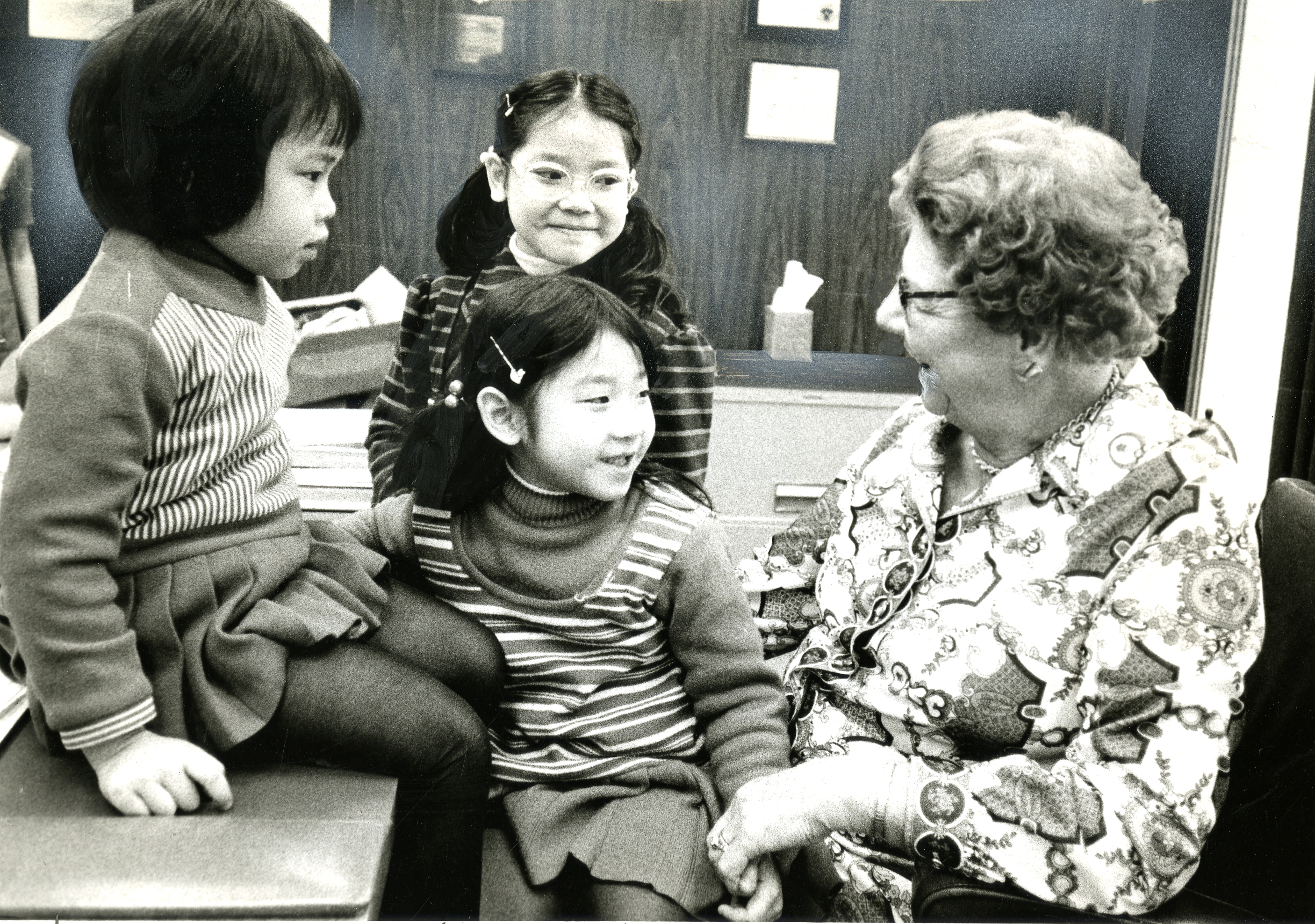 Chan Pui Pui (Dorene), 5, left; Chan Pui Shan, 9, (Irene), standing, and Chan Pui Sai, 7, (Pauline), daughters of brother and Sister Chan Yuk, visit with Sister LaVern Parmley during her trip to Hong Kong in 1974.