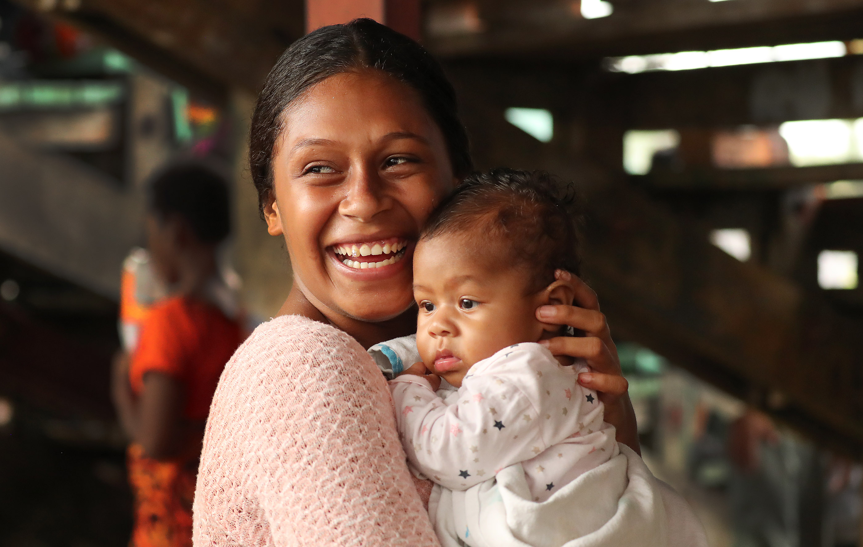 Varanisese Turua holds her daughter Etta Liahona Noa during a devotional at Ratu Cakobau stadium in Nausori, Fiji on May 22, 2019.