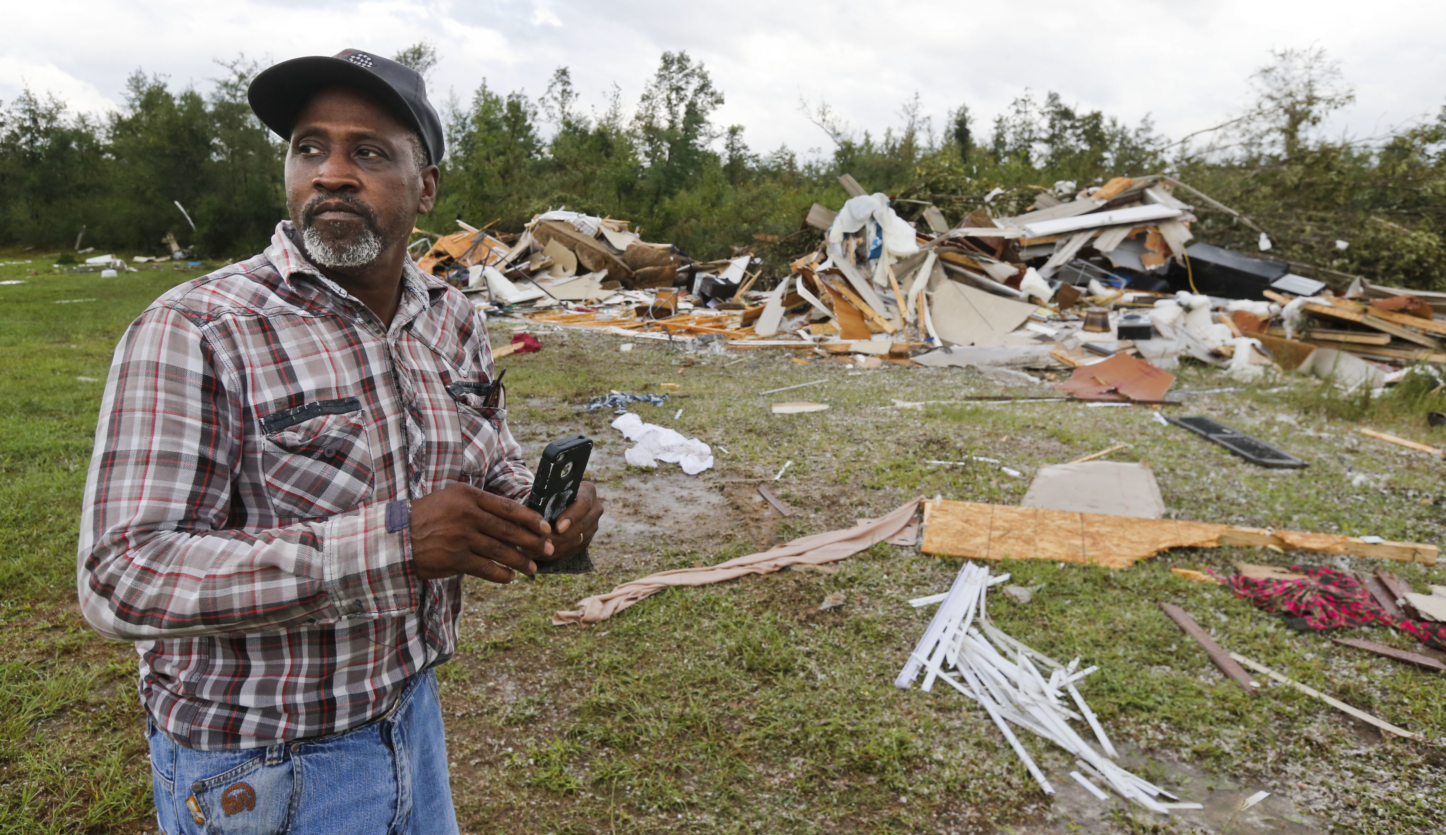 Wayne Doss surveys the damage to his cousin Danny Doss' mobile home, which was completely destroyed by a tornado in Pickens County, Ala., after a tornado struck Thursday, Aug. 31, 2017. The tornado damaged several homes in northwest Alabama as the remnants of Hurricane Harvey came through the state. (Gary Cosby Jr./The Tuscaloosa News via AP)