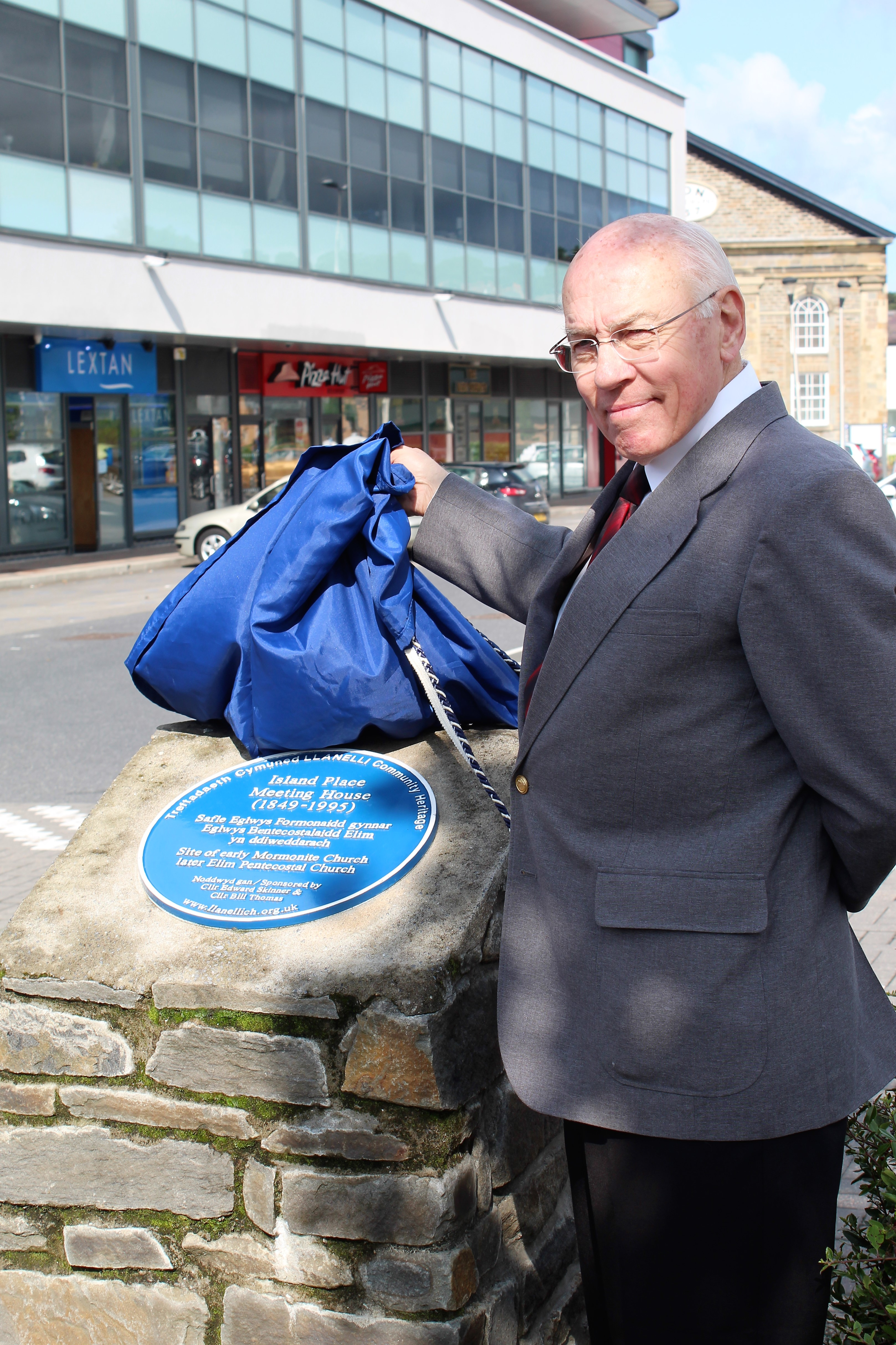 Dr. Ronald Dennis unveils the blue plaque to commemorate the historic Church building known as the Island Place Meeting House on Aug. 25, 2018, in Llanelli, Wales.