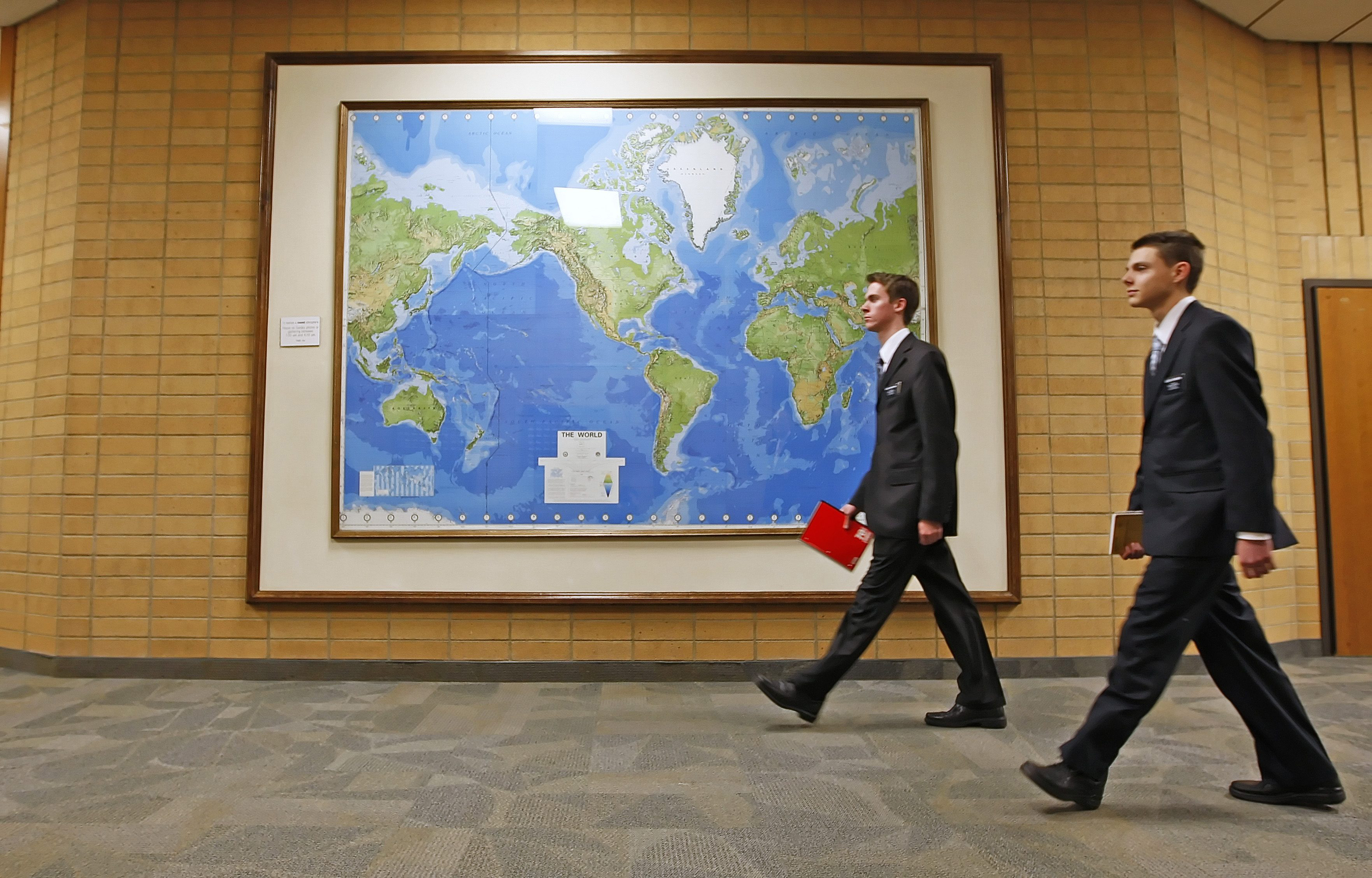 Two Mormon missionaries walk past a large map of the world in a hallway at the Missionary Training Center in Provo, Utah Thursday January 31, 2008. The Mormon church has over 50,000 missionaries at anyone time serving around the world most of who are in their late teens or early 20's. (AP Photo/George Frey)