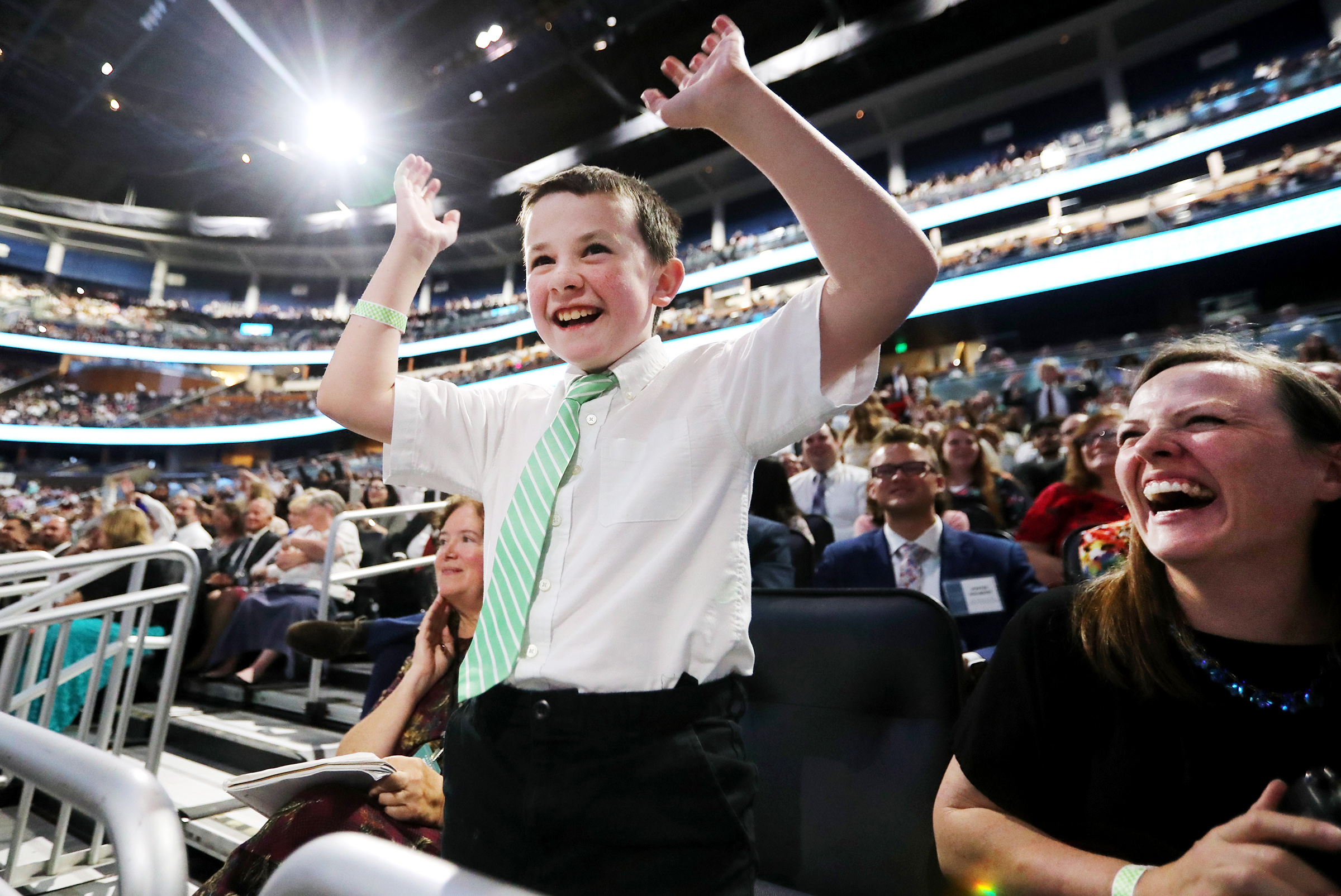 Ethan Meyers waves his arms and his mom, Sarah Meyers, laughs as they listen to President Russell M. Nelson during the devotional at the Amway Center in Orlando, Florida, on Sunday, June 9, 2019.