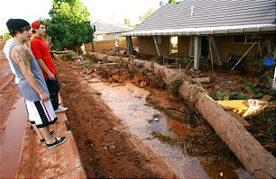 A group of young men stand on what was a brick wall in the back yard of a home in Santa Clara. Thousands of volunteers swarm to help residents in Santa Clara work to clean up after flood waters broke the dike Tuesday, Sept. 11, 2012 and destroyed several homes and businesses.