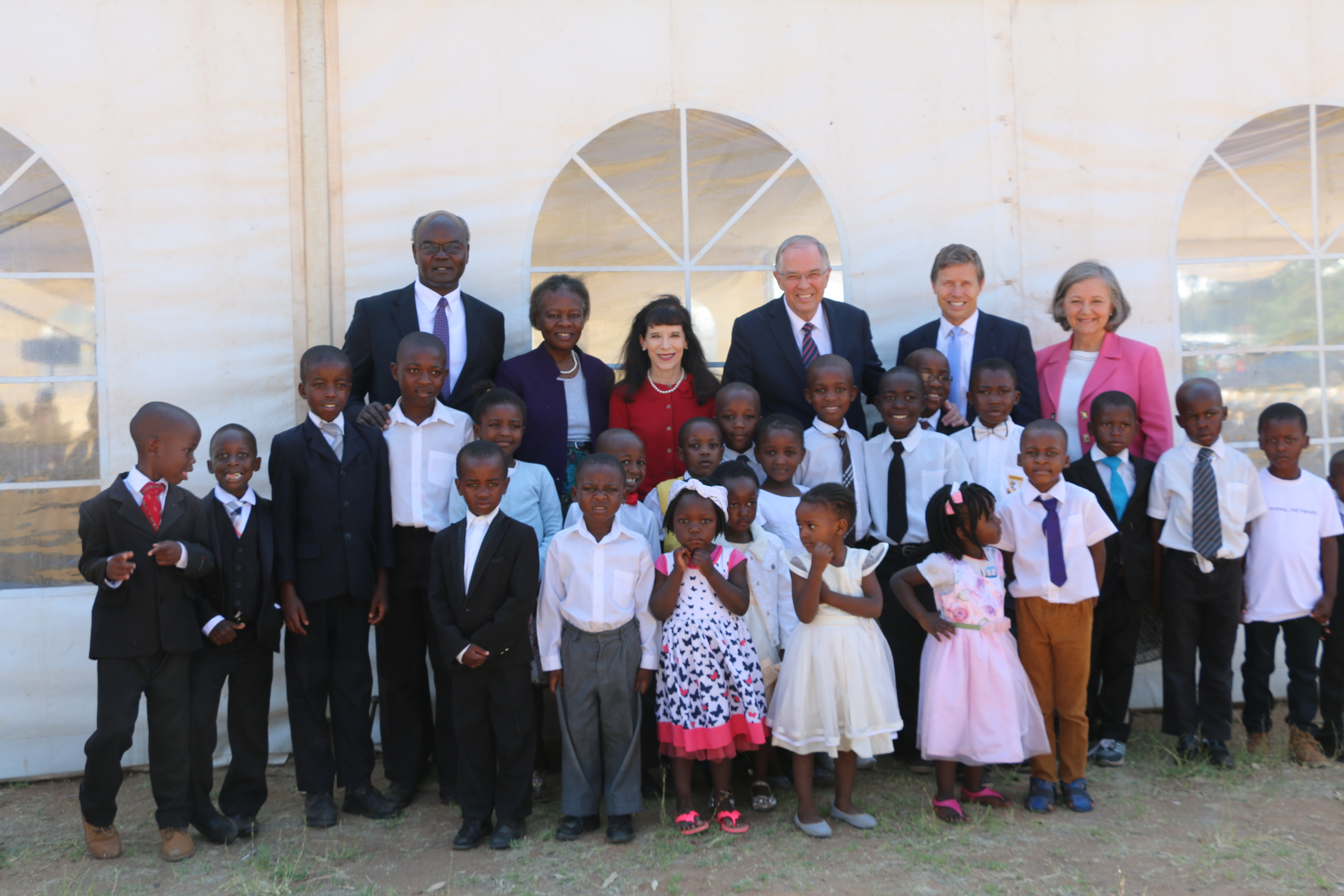 Elder Neil L. Andersen of the Quorum of the Twelve Apostles, center with Sister Kathy Andersen; Elder Jospeh W. Sitati, a General Authority Seventy, and Sister Gladys N. Sitati, left; and Elder S. Mark Palmer, a General Authority Seventy, and Sister Jacqueline W. Palmer, gather with children after a member meeting in Zimbabwe on Nov. 18. 2018.