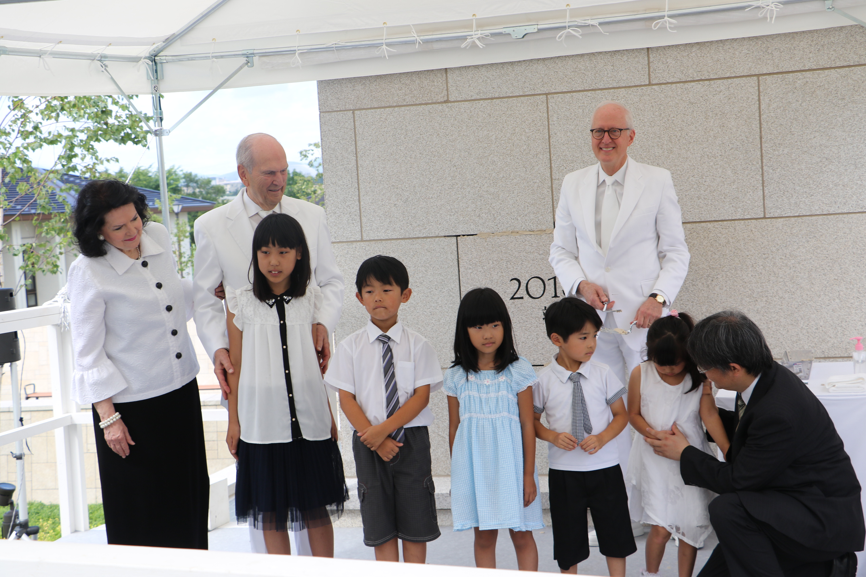 During a cornerstone ceremony for the Sapporo Japan Temple, President Russell M. Nelson and his wife, Sister Wendy Nelson, stand with children invited to participate, from left, Kuhi Kikuchi, 10; Ryuto Miyamoto, 8; Hina Iwamoto, 7; Kaito Miyamoto, 6; and Miku Nigita, 4, who is helped by her father, Haruhiko Nigita. Elder Elder Larry Y. Wilson of the Seventy looks on from behind.