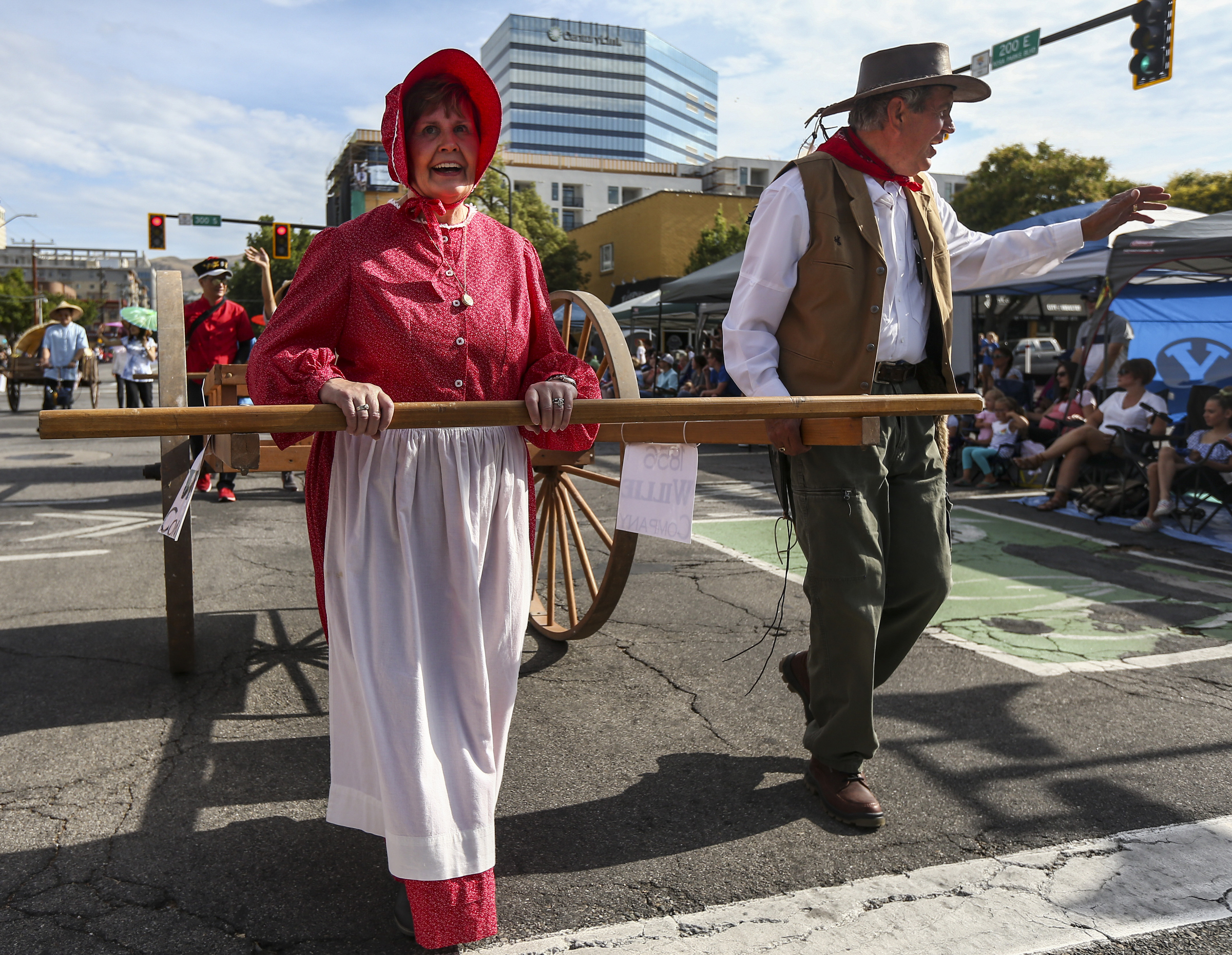 Mark Bezzant, right, and Colleen Bezzant pull a handcart with the Sons of Utah Pioneers during the Days of '47 Parade in Downtown Salt Lake City on Wednesday, July 24, 2019.