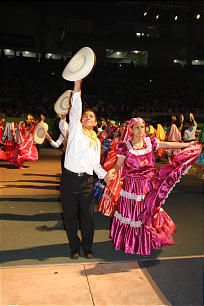 Young performers in traditional Salvadoran dress salute audience members following a spirited dance.