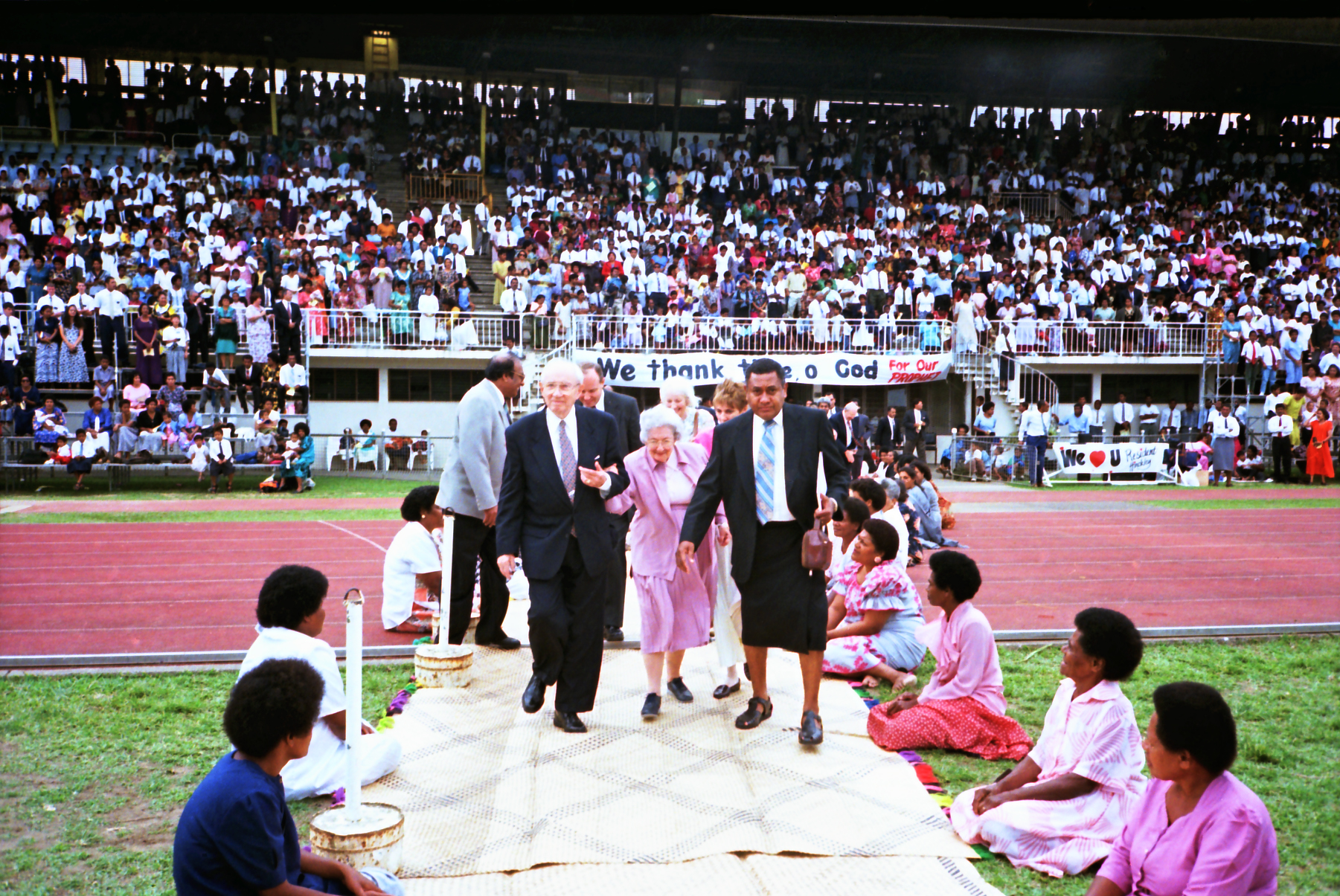 President Gordon B. Hinckley and his wife, Sister Marjorie P. Hinckley, enter National Stadium in Suva, Fiji, on Oct. 15, 1997. They are escorted by one of Fiji's first members of the Church, Joseph Sokia. Fiji was one of eight islands of the Pacific that President Hinckley visited on a week-long tour.