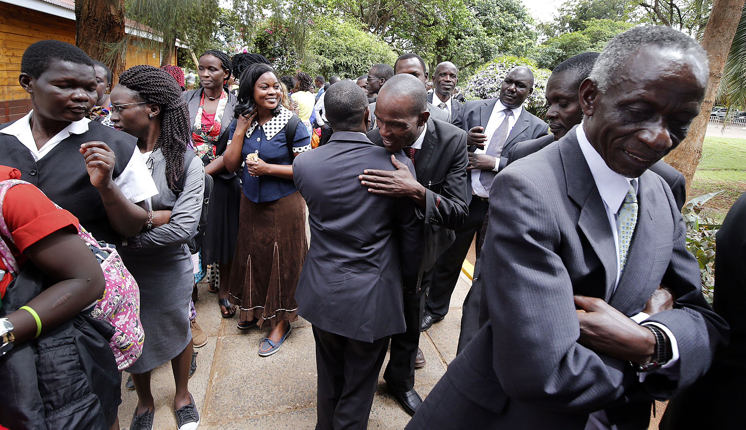 People line up to attend a special devotional with President Russell M. Nelson of The Church of Jesus Christ of Latter-day Saints in Nairobi, Kenya, on Monday, April 16, 2018. At center, Newton Senyange and Moses Mbiro hug.