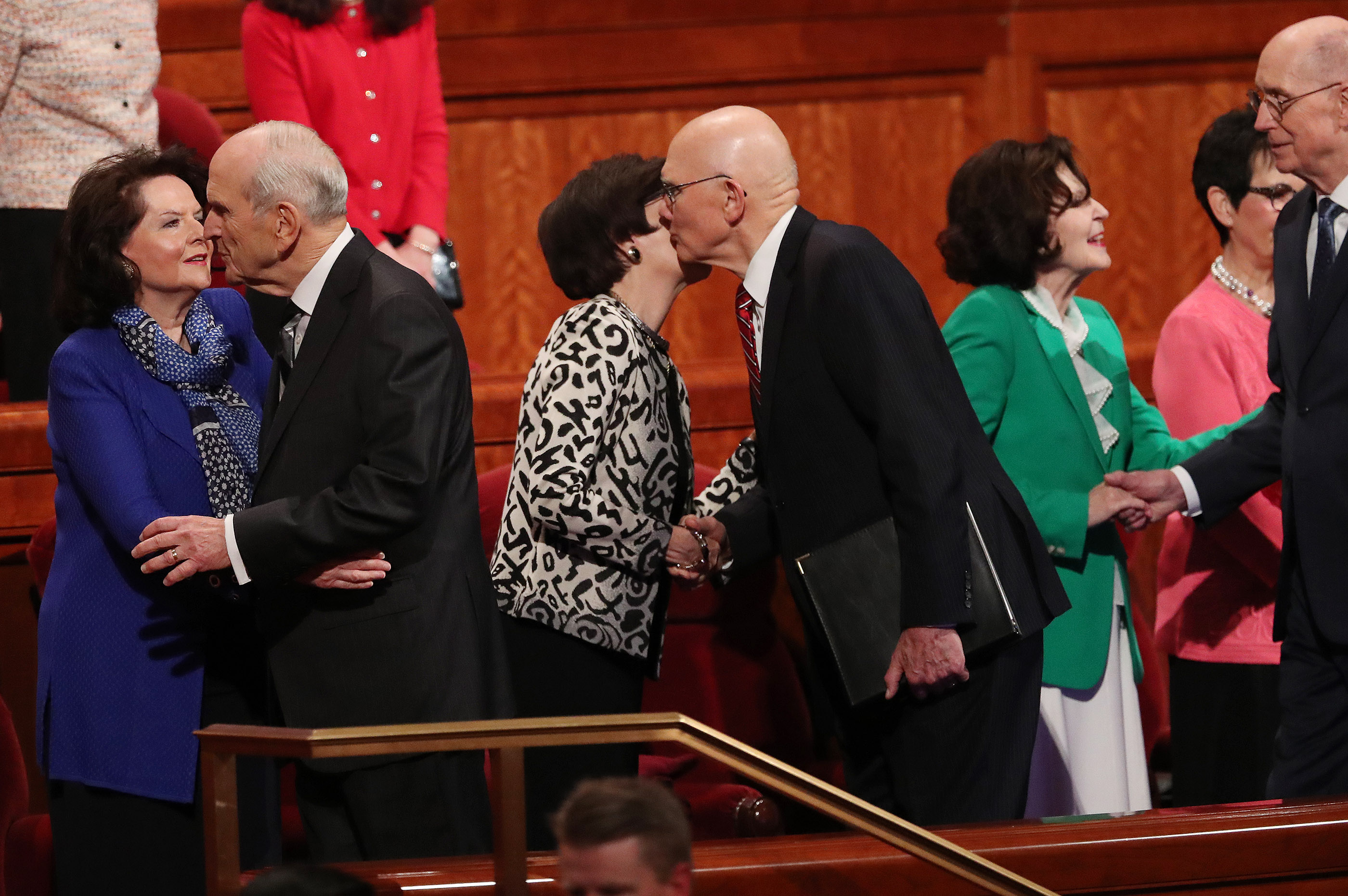 President Russell M. Nelson of The Church of Jesus Christ of Latter-day Saints, left, and his counselor, President Dallin H. Oaks of the First Presidency, greet their wives as second counselor, President Henry B. Eyring, and others enter the Conference Center during the Saturday morning session.