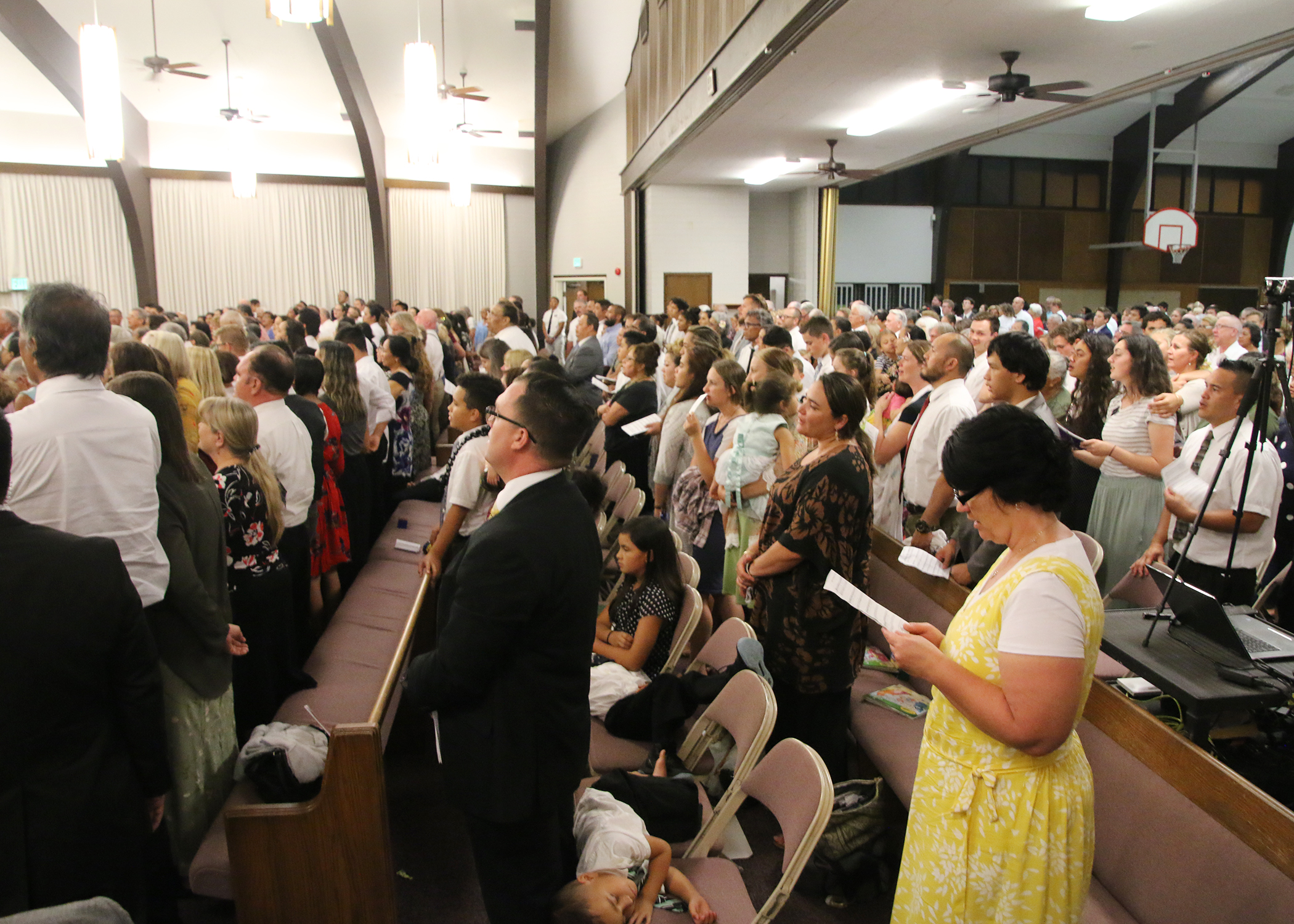 Approximately 1,200 Latter-day Saints, community leaders and a Tongan interfaith choir sing during a May 16, 2019, devotional at the Kona Hawaii Stake Center with President Russell M. Nelson, his wife, Sister Wendy Nelson; Elder Gerrit W. Gong of the Quorum of the Twelve Apostles; and his wife, Sister Susan Gong.
