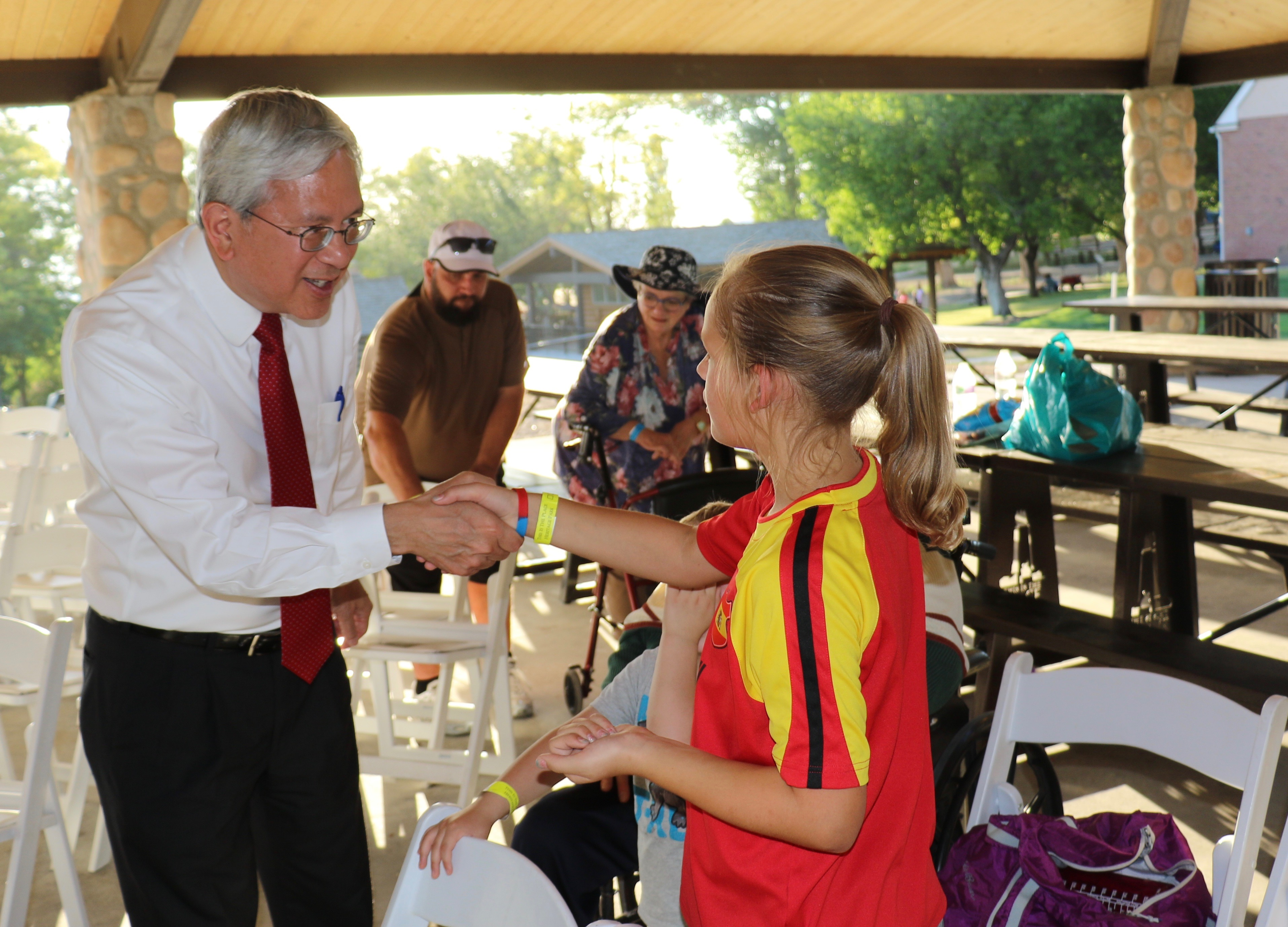 Elder Gerrit W. Gong introduces himself to 10-year-old Miriam Hurd prior to the July 16, 2018, devotional at This Is the Place Heritage Park.