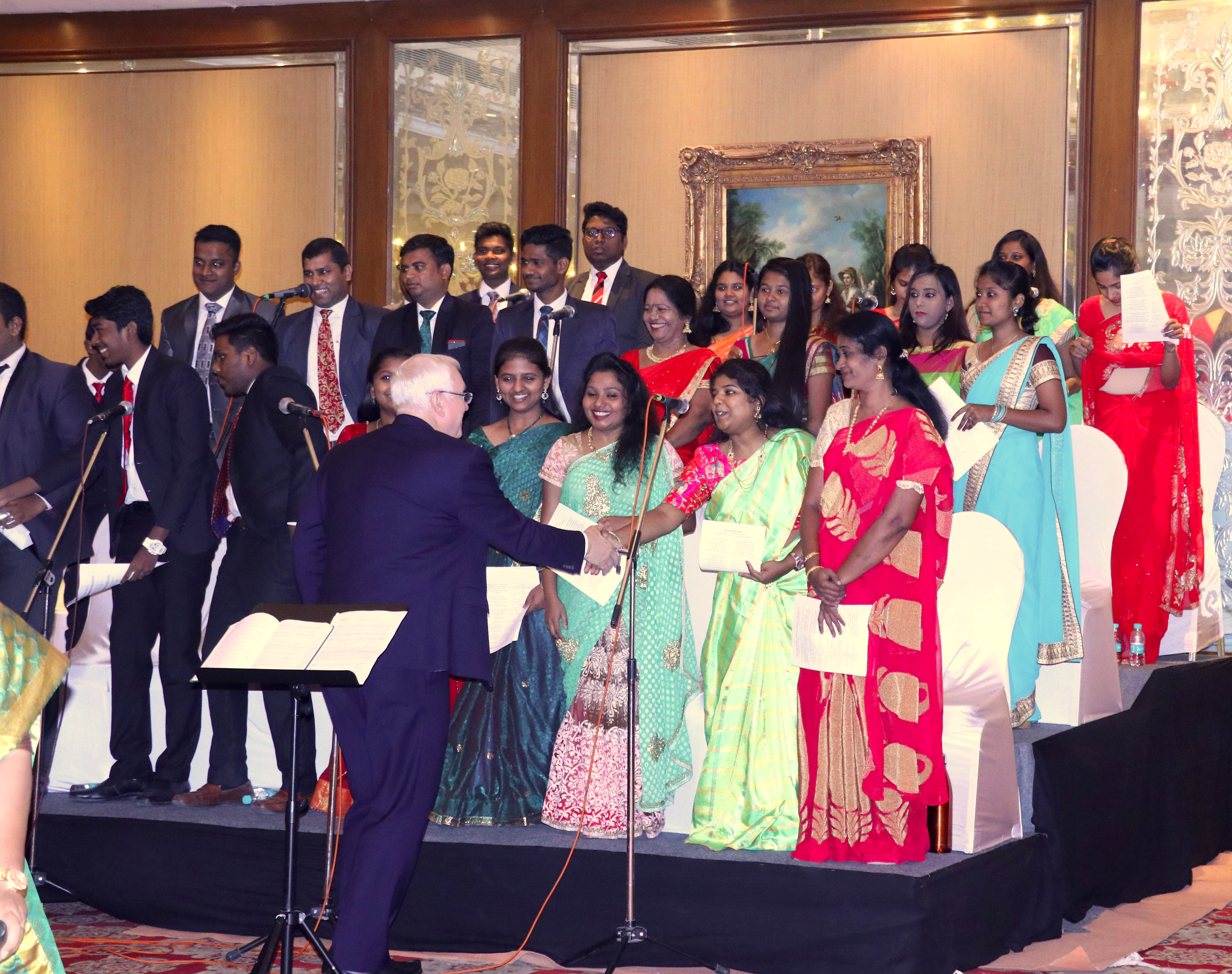Elder Robert C. Gay shakes hands with members of the choir during a meeting with members in Hyderabad, India, in May 2019.