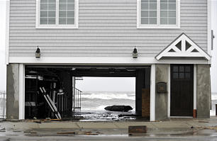 A piece of drift wood sits in the garage of a beachside home in Milford, Conn., Monday, Oct. 29, 2012. Hurricane Sandy continued on its path Monday, as the storm forced the shutdown of mass transit, schools and financial markets, sending coastal residents fleeing, and threatening a dangerous mix of high winds and soaking rain.