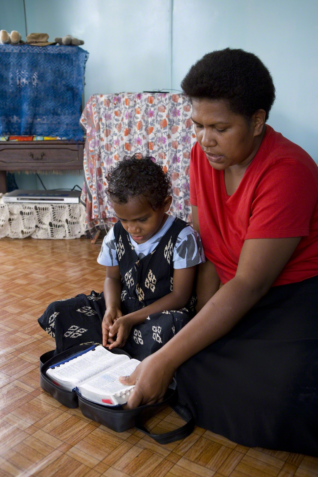 A mother and her daughter sit on the floor and read the scriptures.