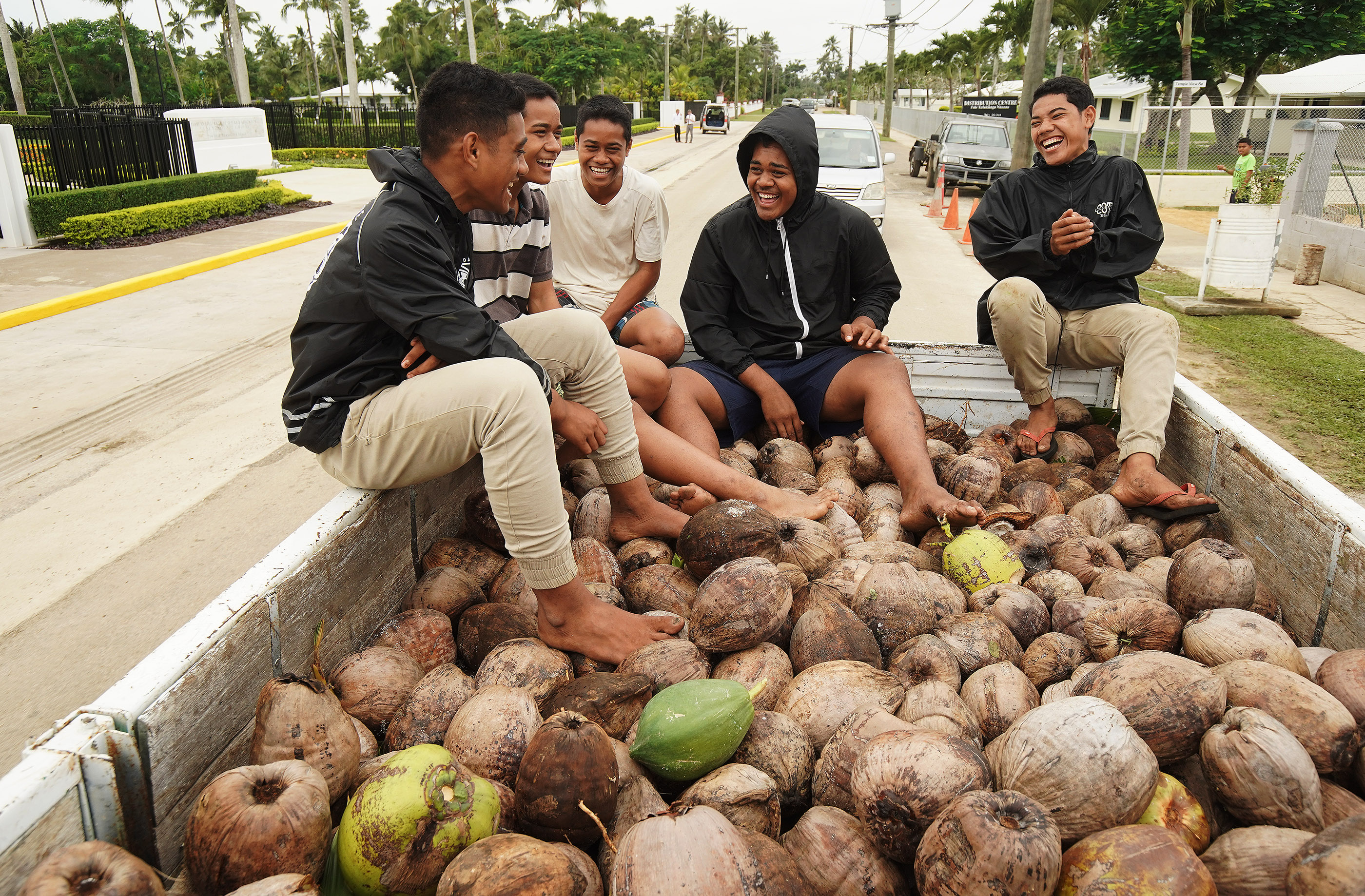Coconut pickers ride in the back of a truck in Tonga on May 23, 2019.