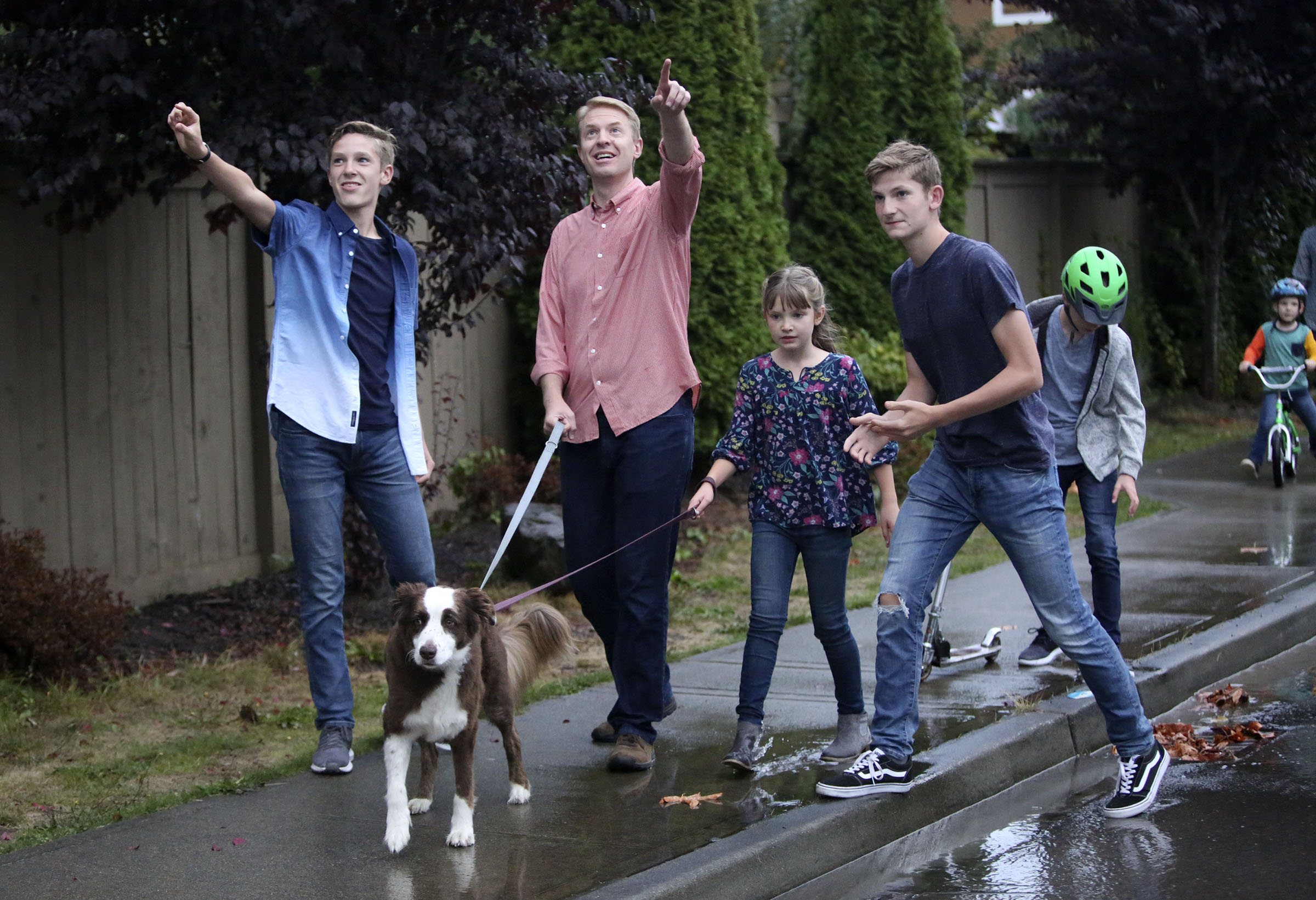 Jonathan, Justin, Emilia, and Ben Allen watch storm clouds in the distance while walking home with their dog Lou in Renton, Wash., on Friday, Sept. 14, 2018.