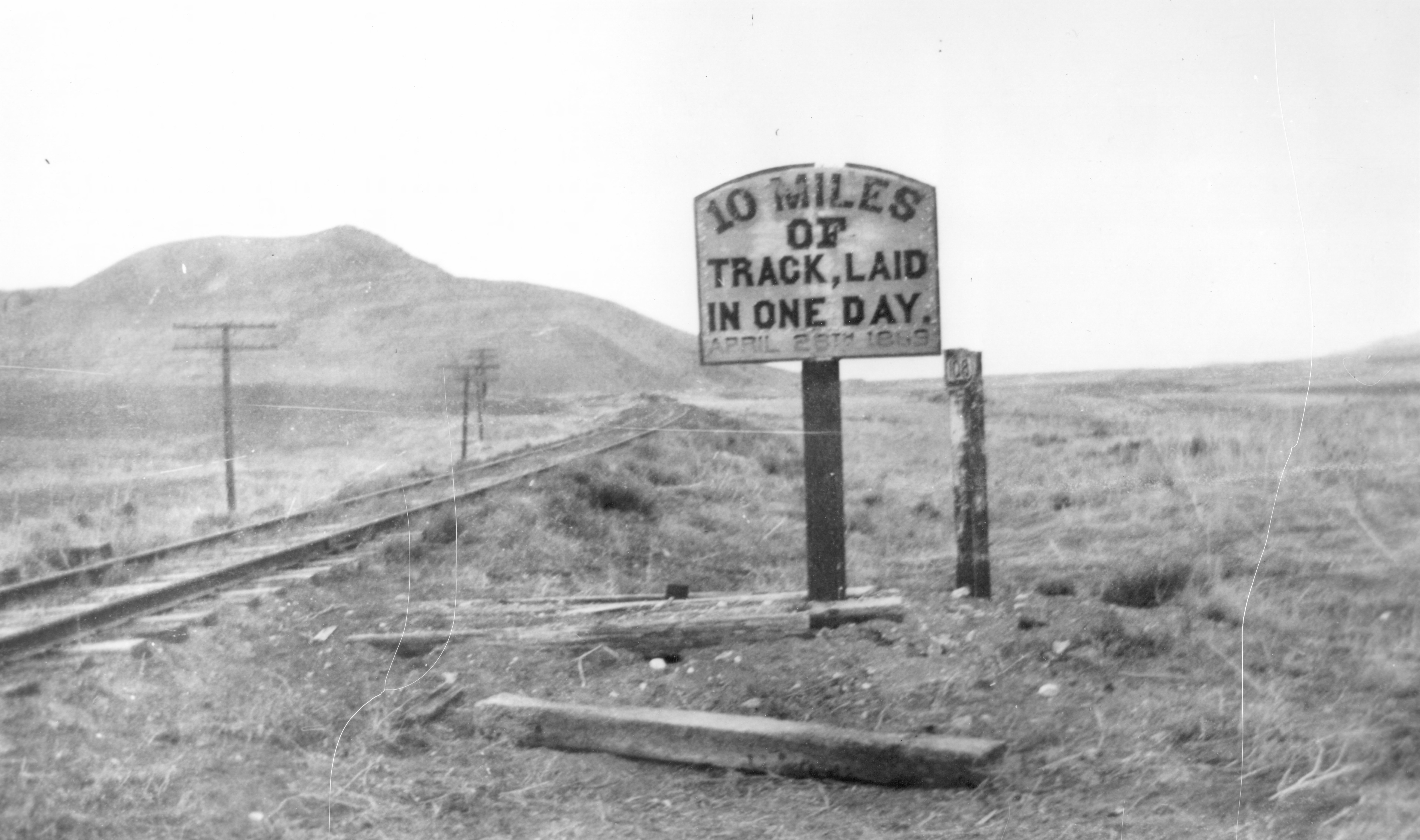 """A sign marks a construction site of Central Pacific Railroad, reading: """"10 miles of track, laid in one day, April 28th, 1869."""""""
