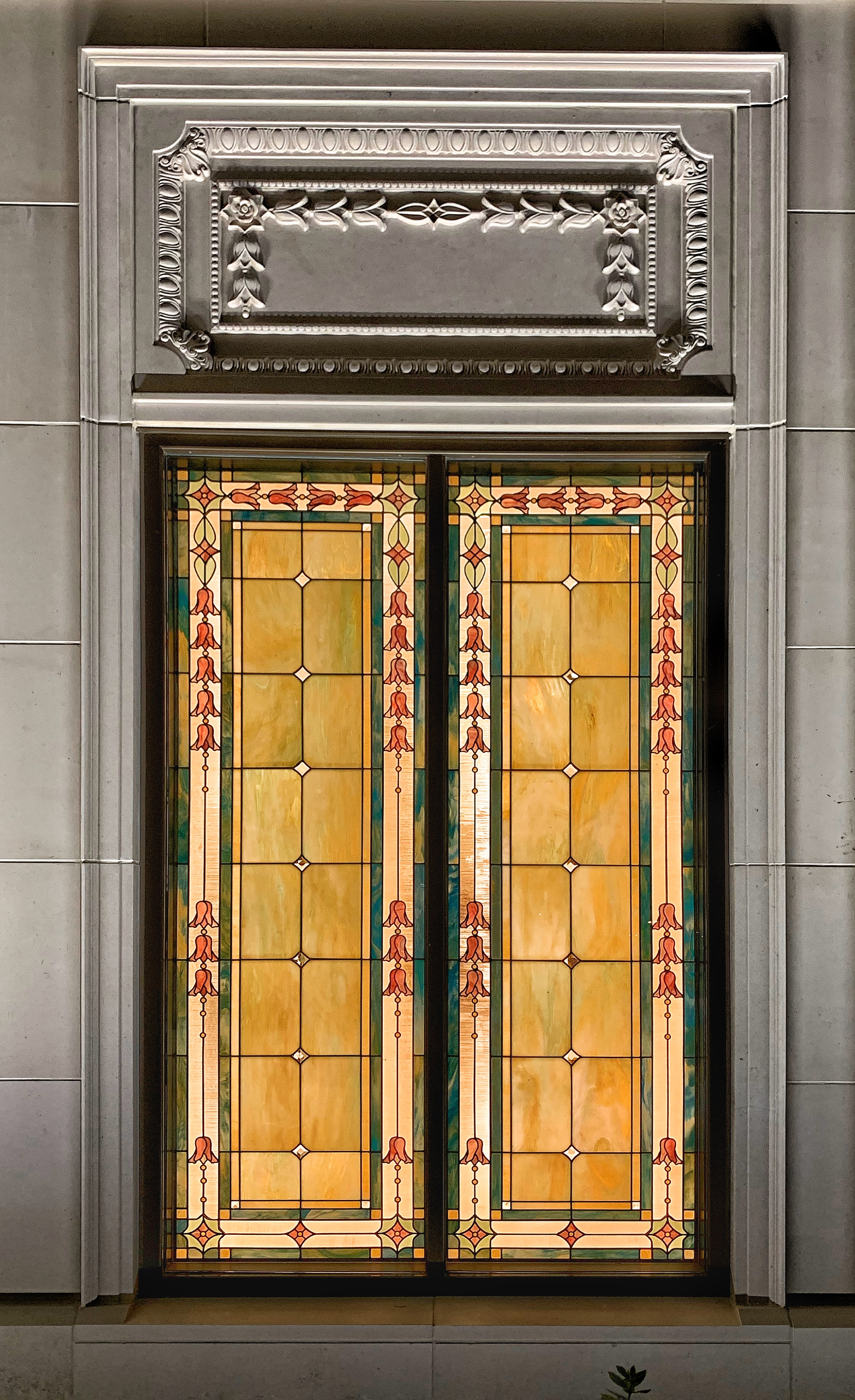 A view of the custom windows on the recently renovated Memphis Tennessee Temple seen from the outside at night. The windows feature the pawpaw flower.