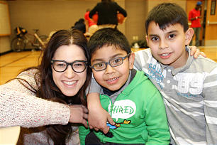 Kristin Robinson interacts with Clever Clark, 7, and Erick Chabert, 10, during Hotdogs and Homework.