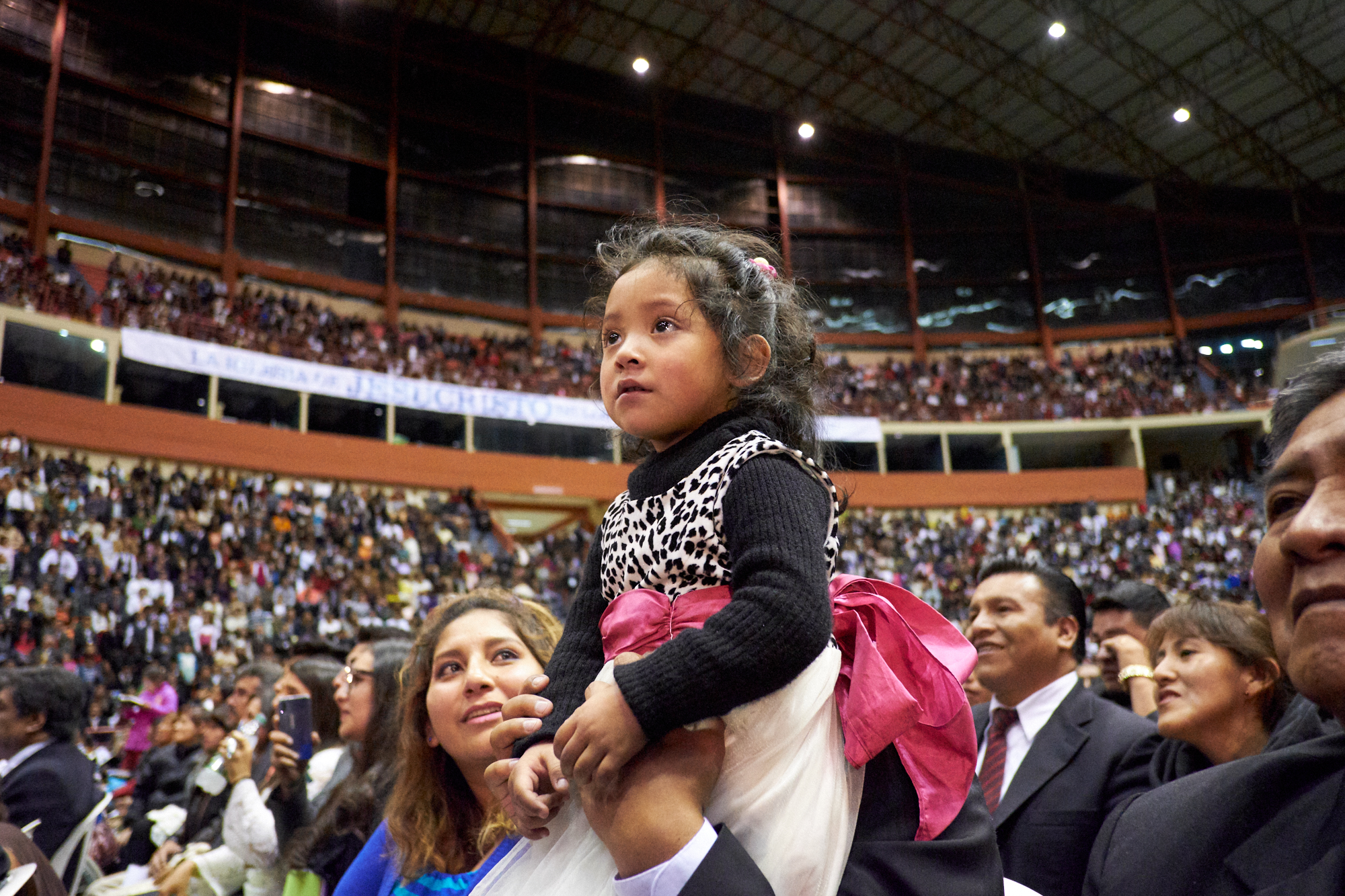 A dad gives his daughter a boost above the crowd to get a better look at President Russell M. Nelson, during a Sunday devotional in the Polideportivo Heroes de Octobre in El Alto, Bolivia, on Oct. 21, 2018.
