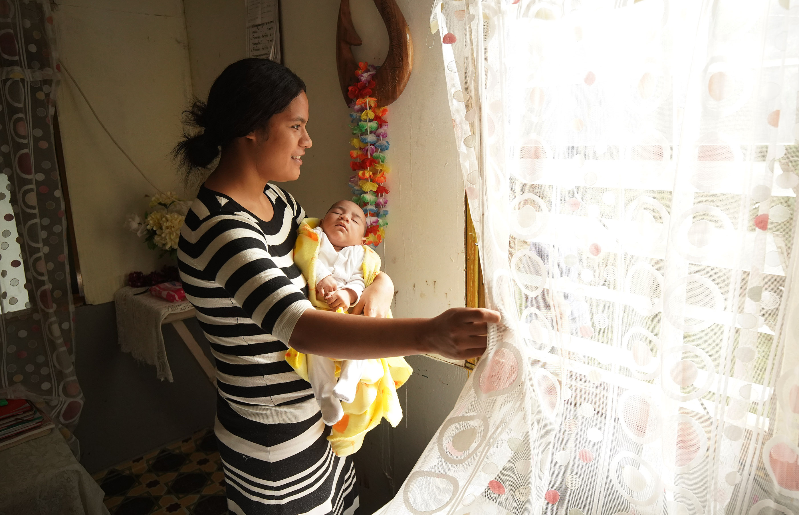 Tohiminiti Latu's daughter-in-law Seini Latu and granddaughter Orson look out of the window in Tonga on May 23, 2019. Tohiminiti Latu is bishop of his ward and has 10 children and one grandchild.