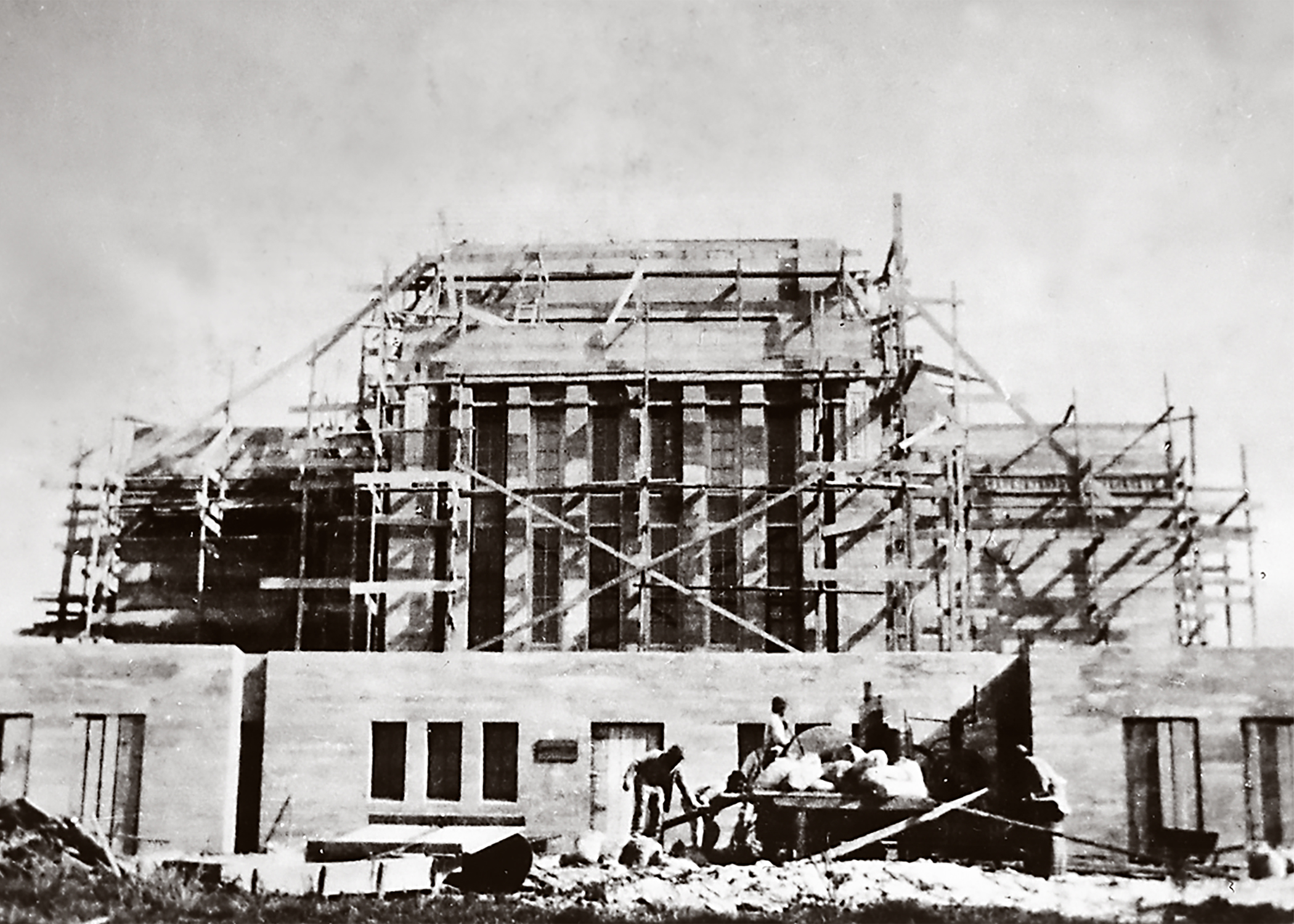 This 1916 photo shows workers preparing material to finish raising the walls of the Laie Hawaii Temple. The Church contracted with a contemporary Massachusetts Institute of Technology (MIT) engineering graduate who had returned home to Honolulu just prior to this to use the then-new technique of poured-in-place cement with steel reinforcing rods (rebar) on the project. Almost all of the work, however, had to be done by hand, without the use of power tools.