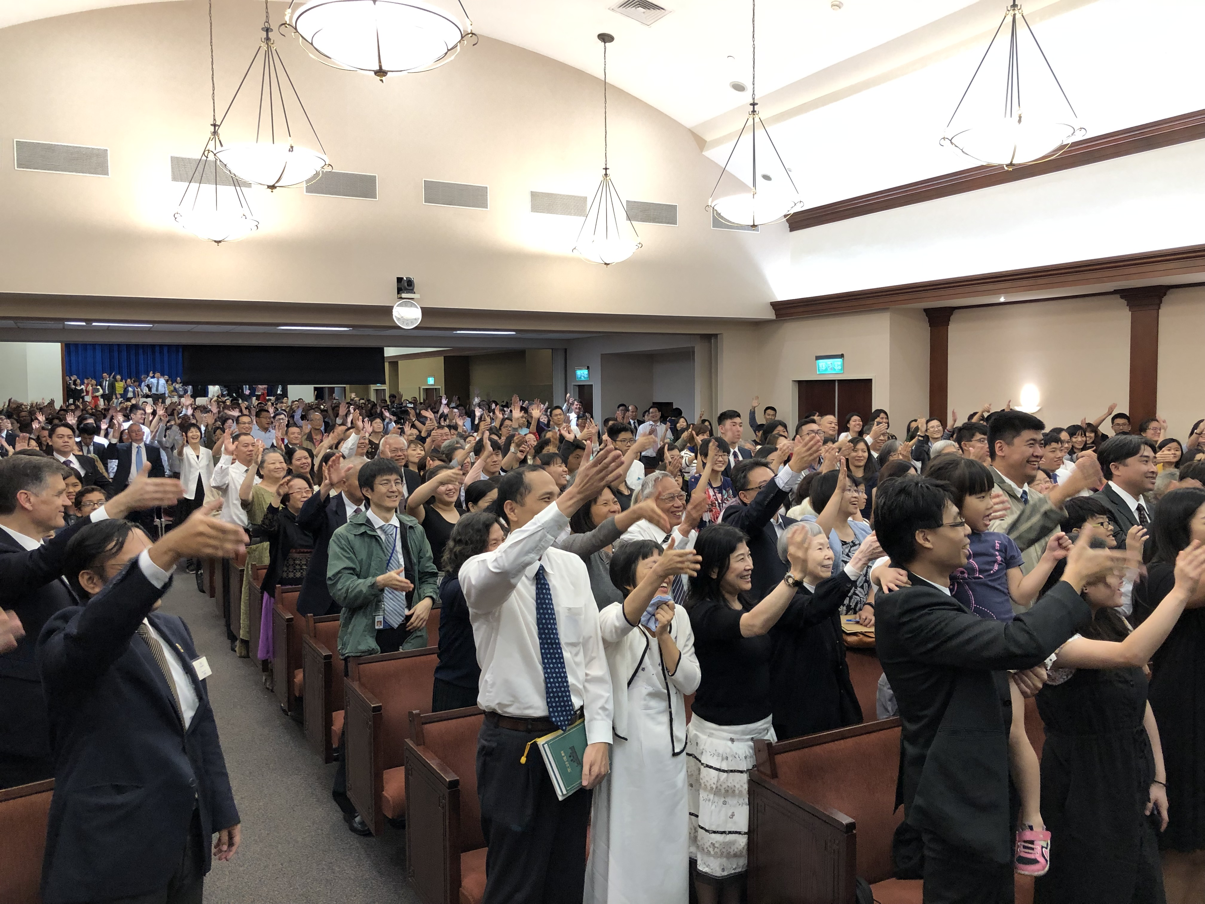 During a member devotional in Taipei, Taiwan, members hold up their hands to do an air handshake with President M. Russell Ballard who was speaking on the stand in May 2019.