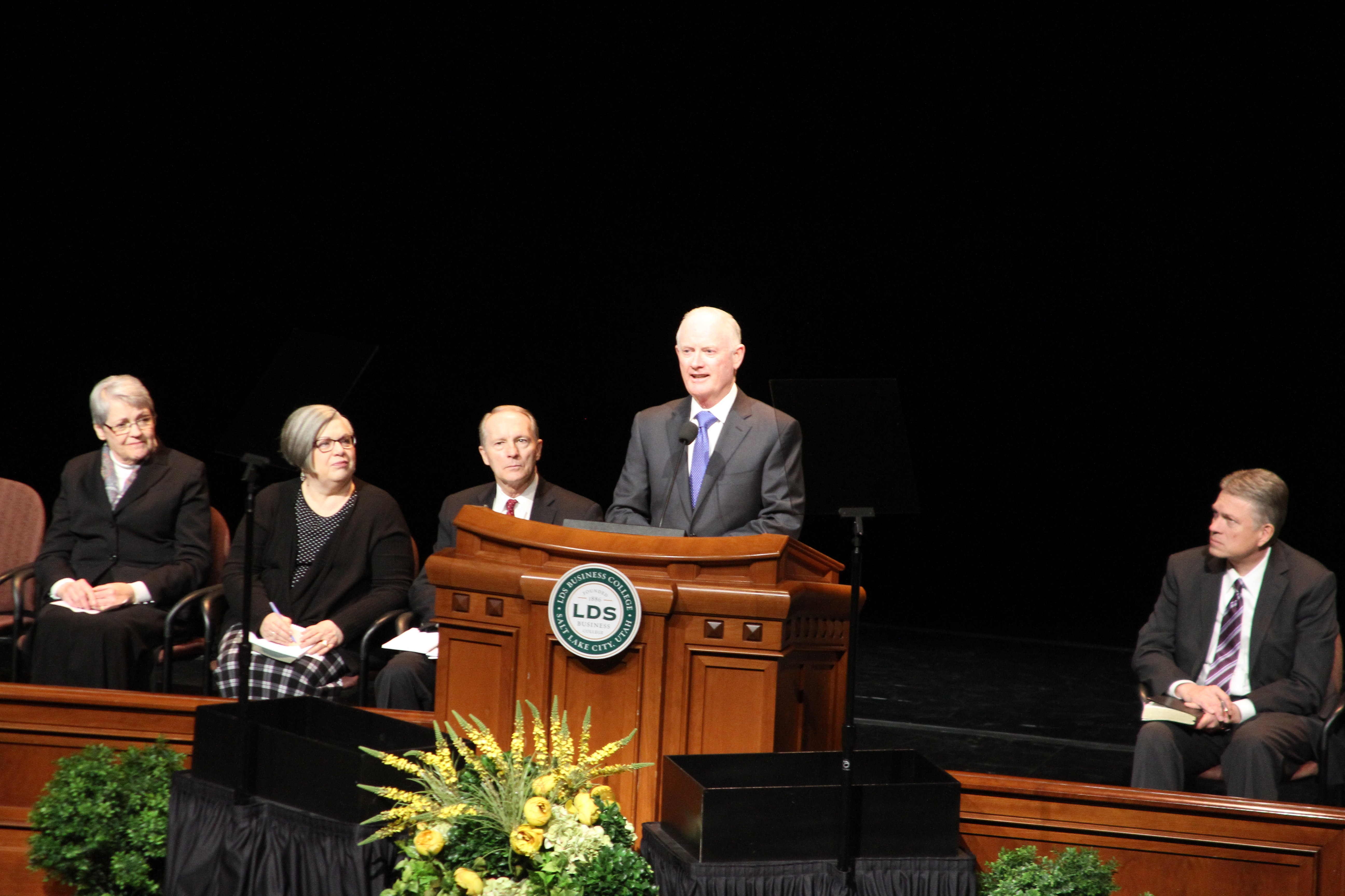 Elder Kim B. Clark, General Authority Seventy and Commissioner of Church Education, introduces his wife, Sister Sue Clark, before her LDS Business College devotional address in the Conference Center Theater on Feb. 19, 2019.