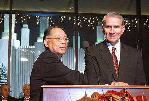 Ambassador Willy C. Gaa, left, and Elder Jay E. Jensen, right, press a button that ignites a half million Christmas lights at the Washington, D.C. Temple and Visitors Center.